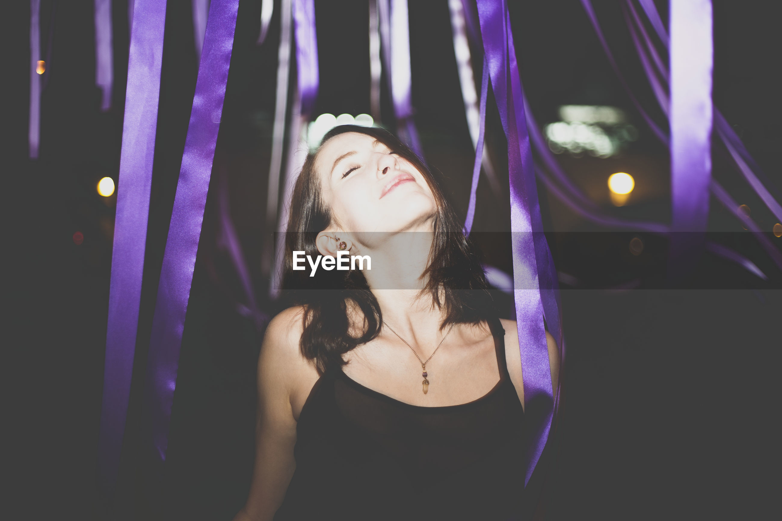 Beautiful young woman with eyes closed standing amidst purple ribbons at night
