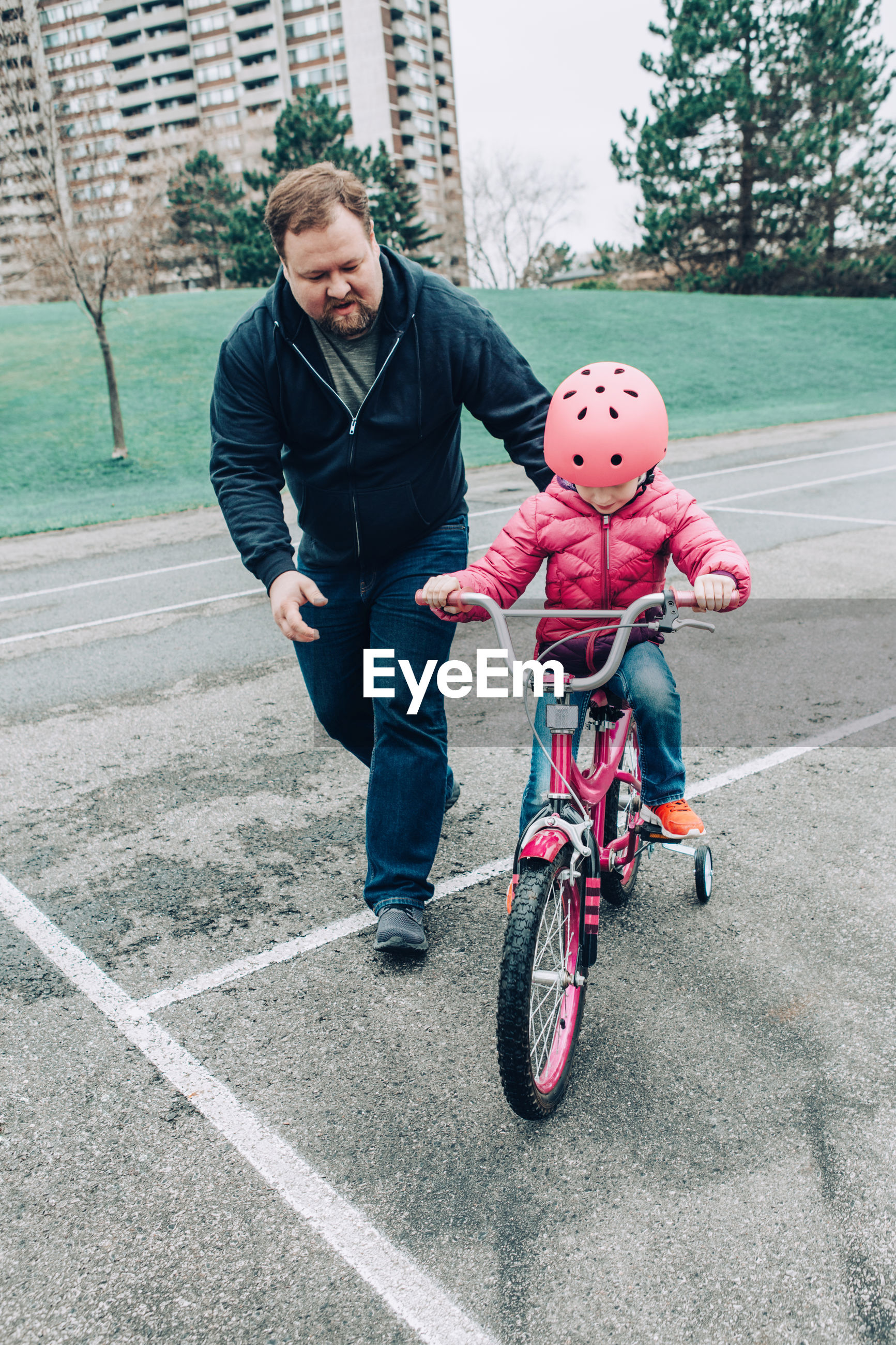 Full length of man assisting daughter in riding bicycle on walkway