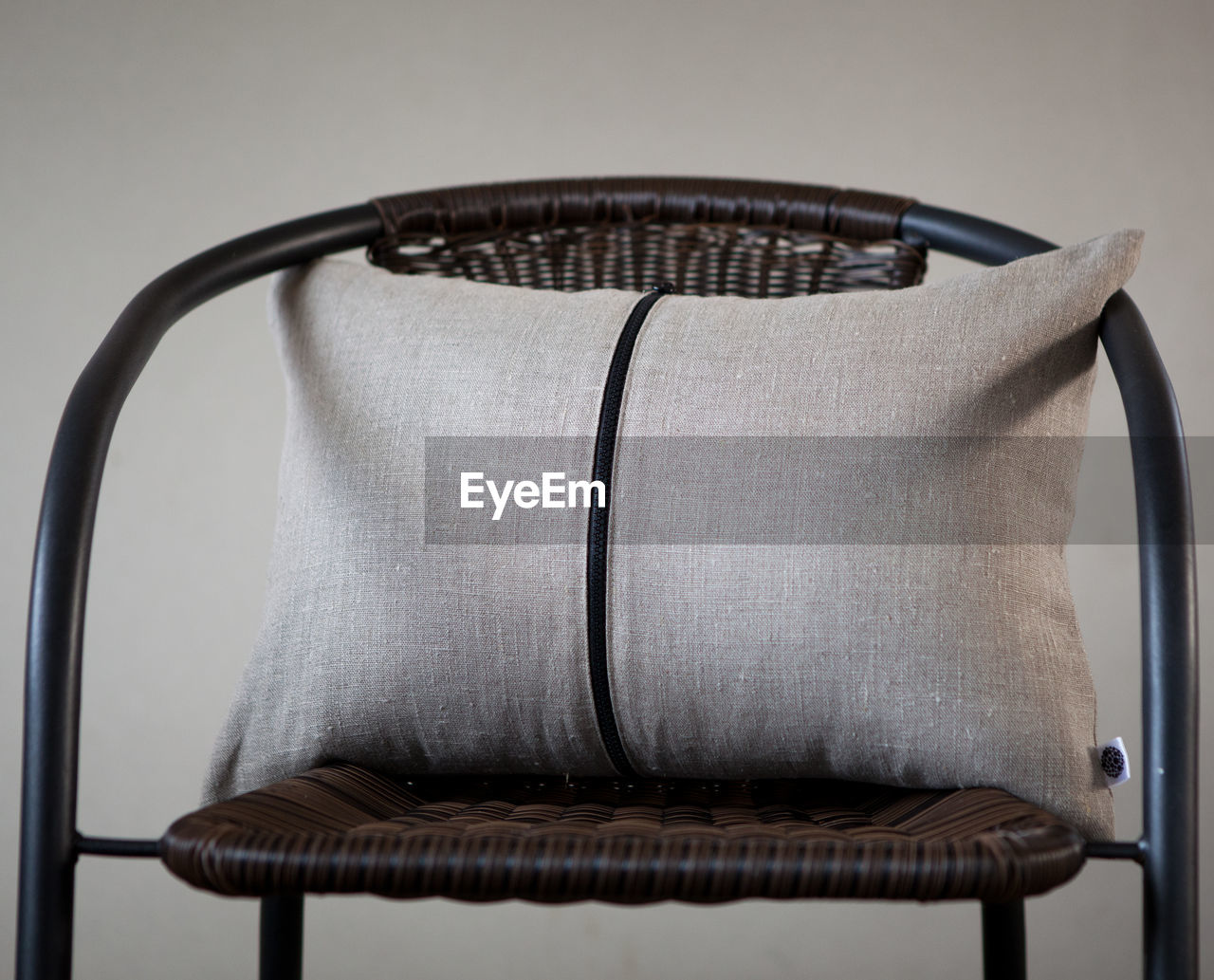 Close-Up Of Pillow On Chair Against Wall