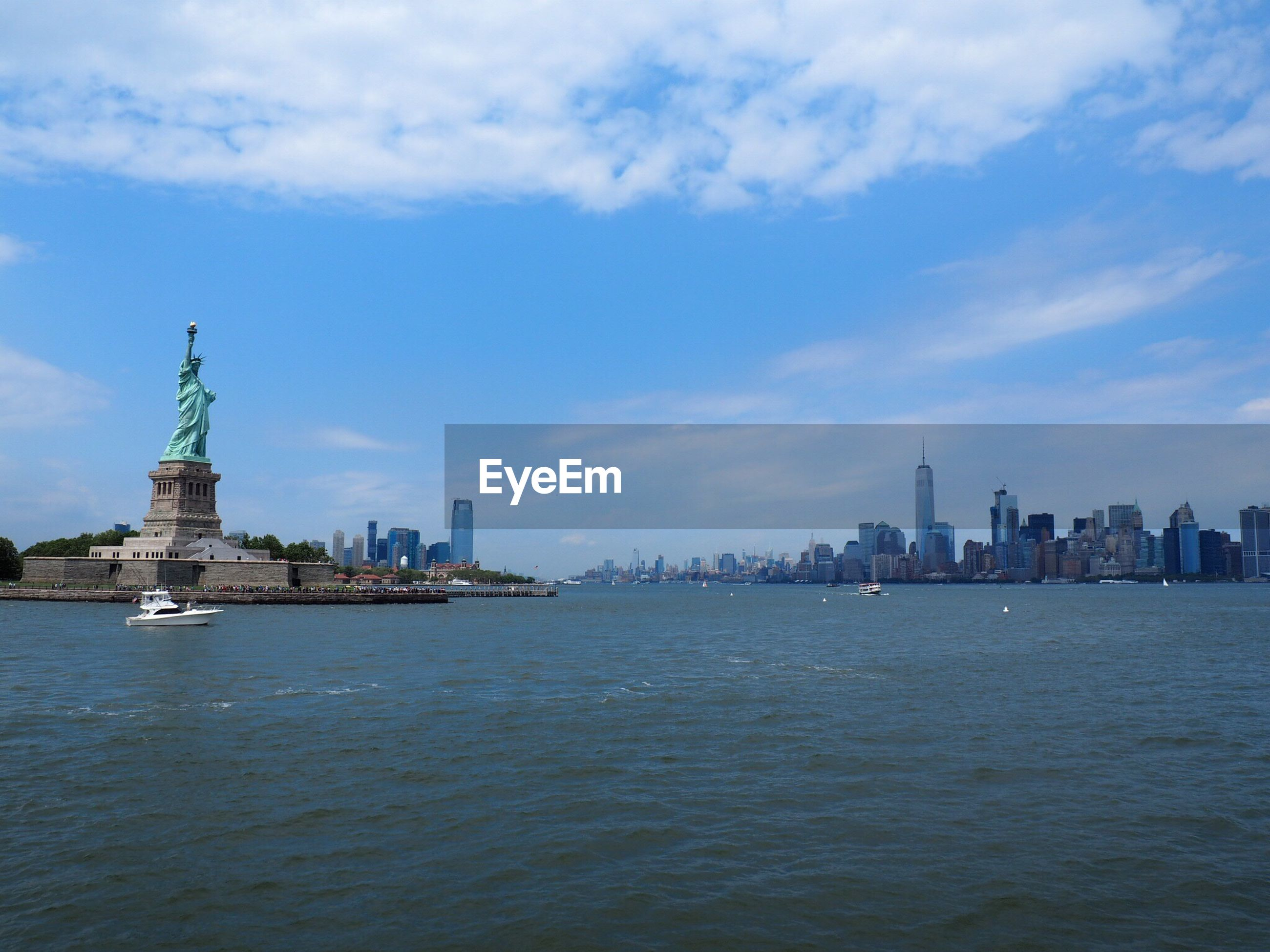 water, architecture, waterfront, built structure, sky, city, travel destinations, river, cloud - sky, capital cities, cityscape, blue, rippled, tourism, cloud, tall - high, day, outdoors, no people, urban skyline, nature, statue of liberty, city life