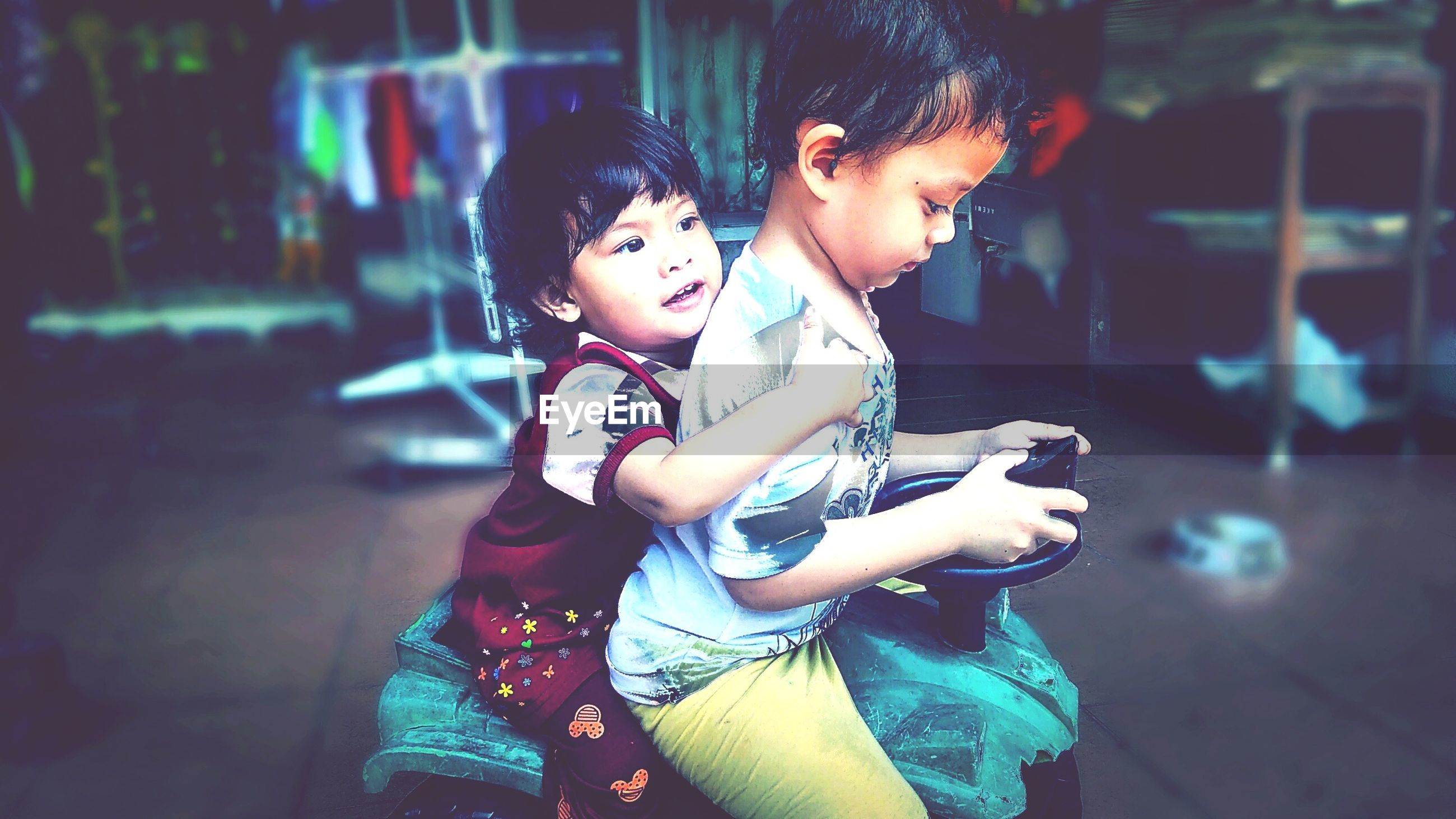 Siblings sitting on toy vehicle at home