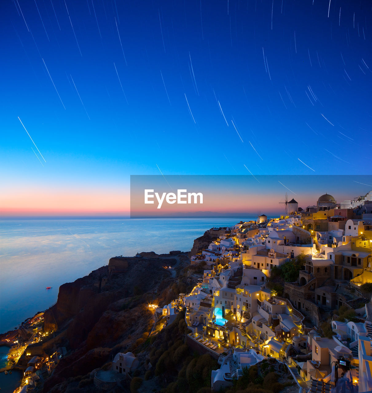 Town By Sea Against Star Trails