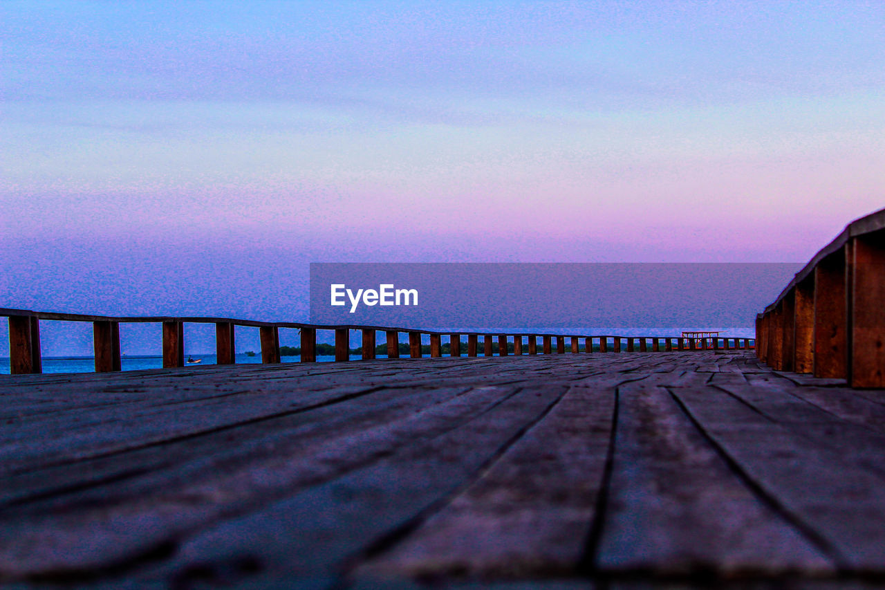 sky, built structure, architecture, cloud - sky, nature, water, railing, sunset, wood - material, no people, pier, selective focus, connection, surface level, beauty in nature, direction, outdoors, bridge, tranquil scene, diminishing perspective, long