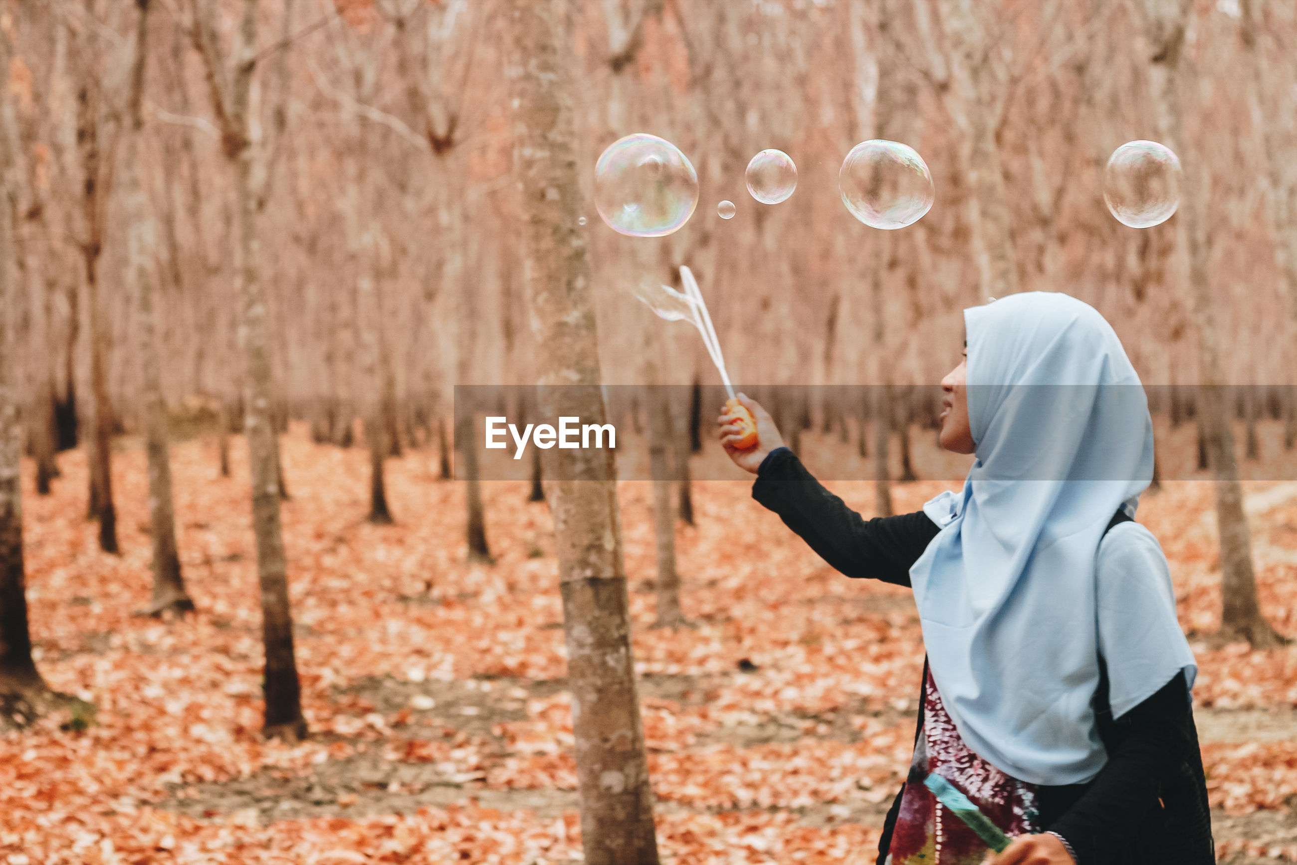 Woman looking at bubbles in forest