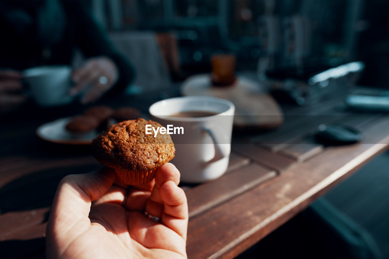food and drink, human hand, hand, holding, one person, real people, food, human body part, freshness, focus on foreground, indoors, drink, sweet food, table, cup, refreshment, lifestyles, unrecognizable person, coffee, coffee cup, temptation, finger, non-alcoholic beverage, snack