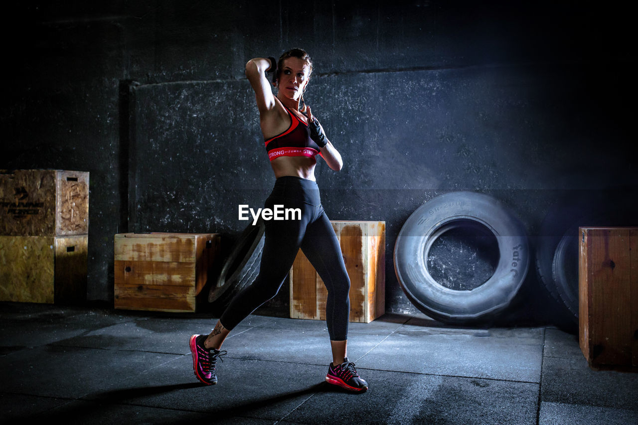 Woman with arms raised practicing aero box, strong by zumba