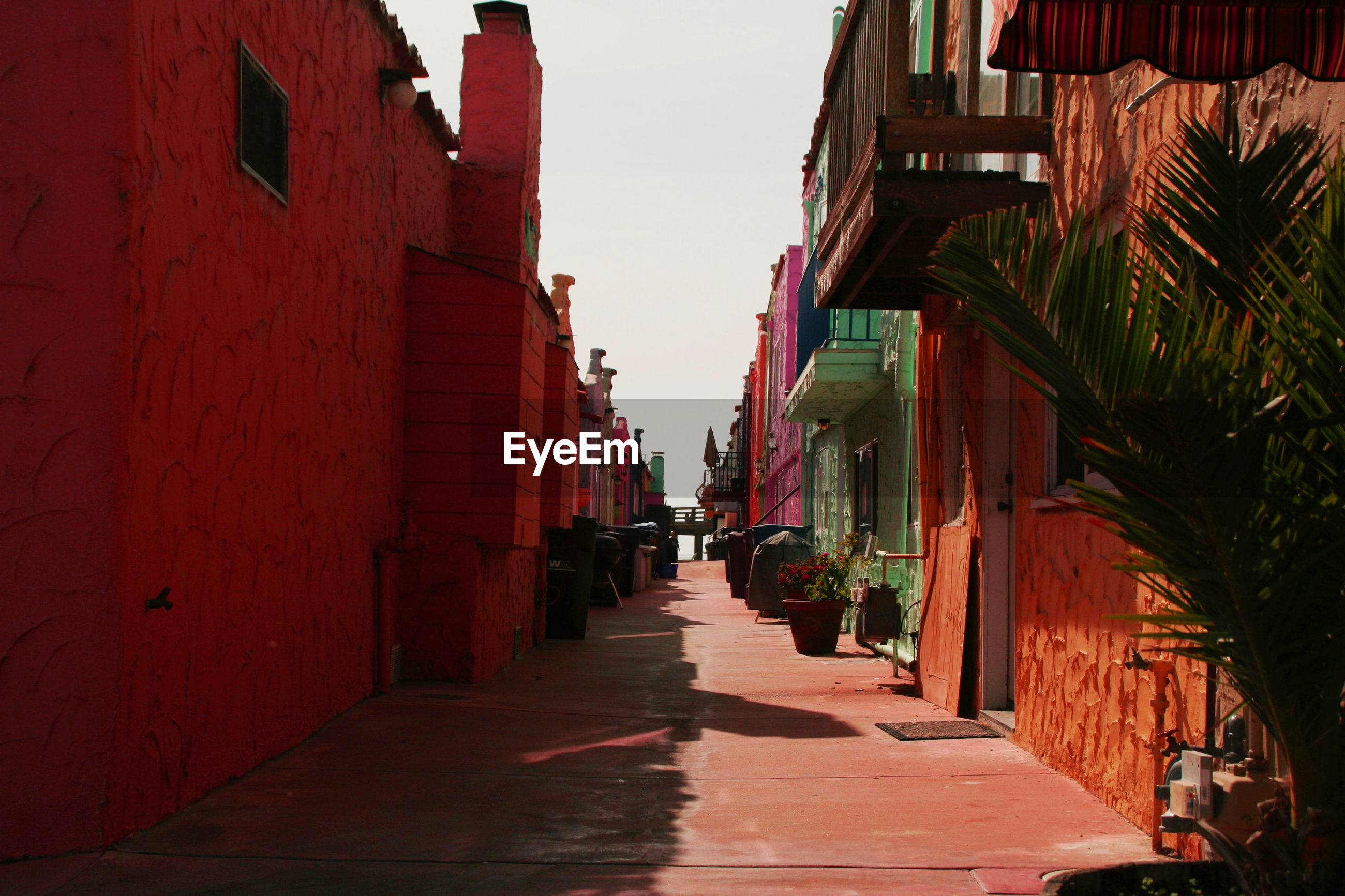 Alley amidst red houses against sky