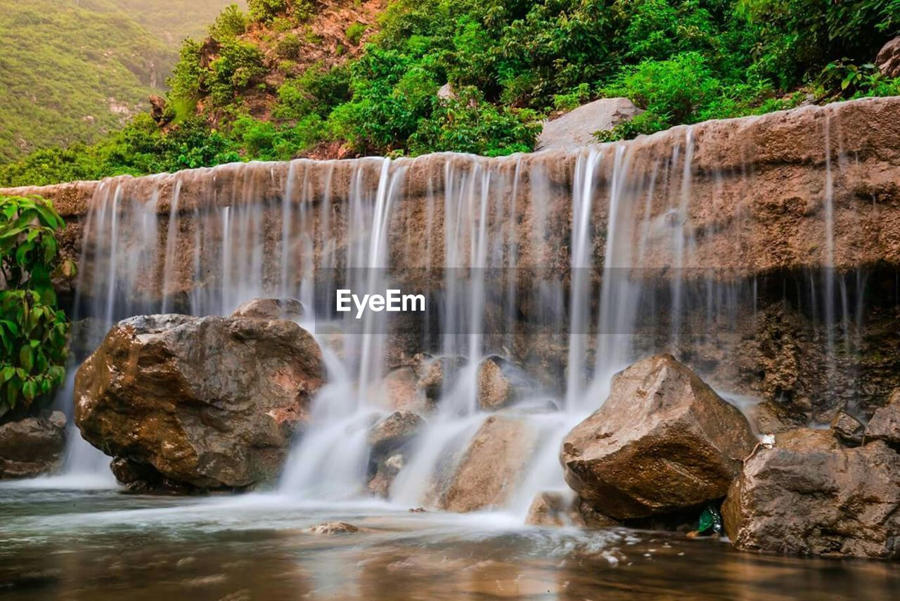 waterfall, motion, water, long exposure, flowing water, rock - object, rock formation, scenics, nature, beauty in nature, river, day, blurred motion, tree, no people, outdoors, travel destinations, waterfront, rapid, forest, cliff, power in nature