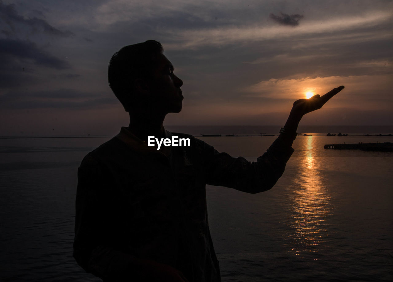 Optical Illusion Of Silhouette Man Holding Sun At Beach Against Sky During Sunset