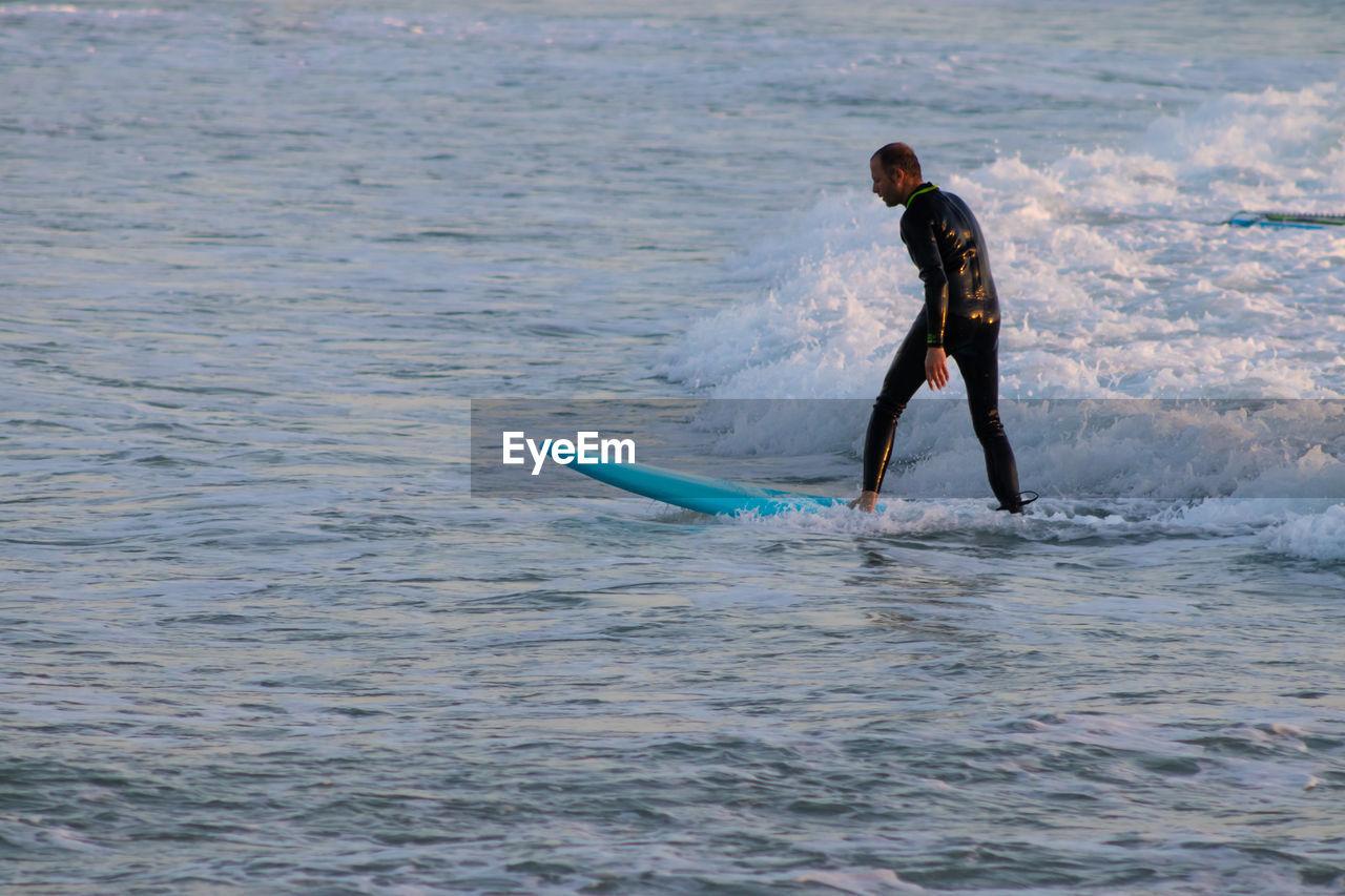 FULL LENGTH OF MAN SURFING