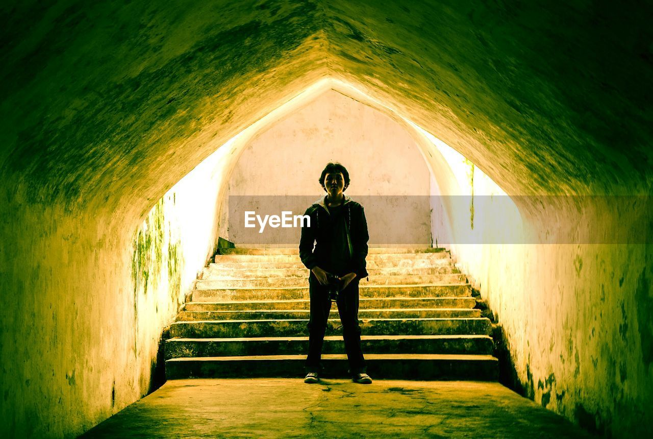 Man Standing In Tunnel