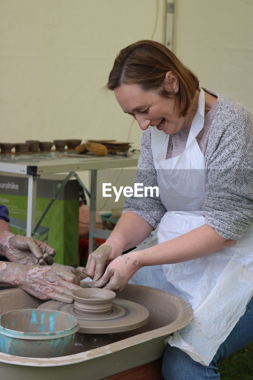 Smiling Mature Woman Shaping Clay On Pottery Wheel By Cropped Man In Workshop
