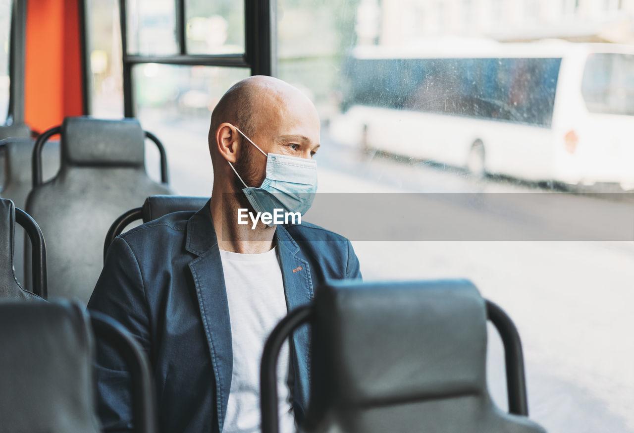 Man wearing mask while traveling in bus