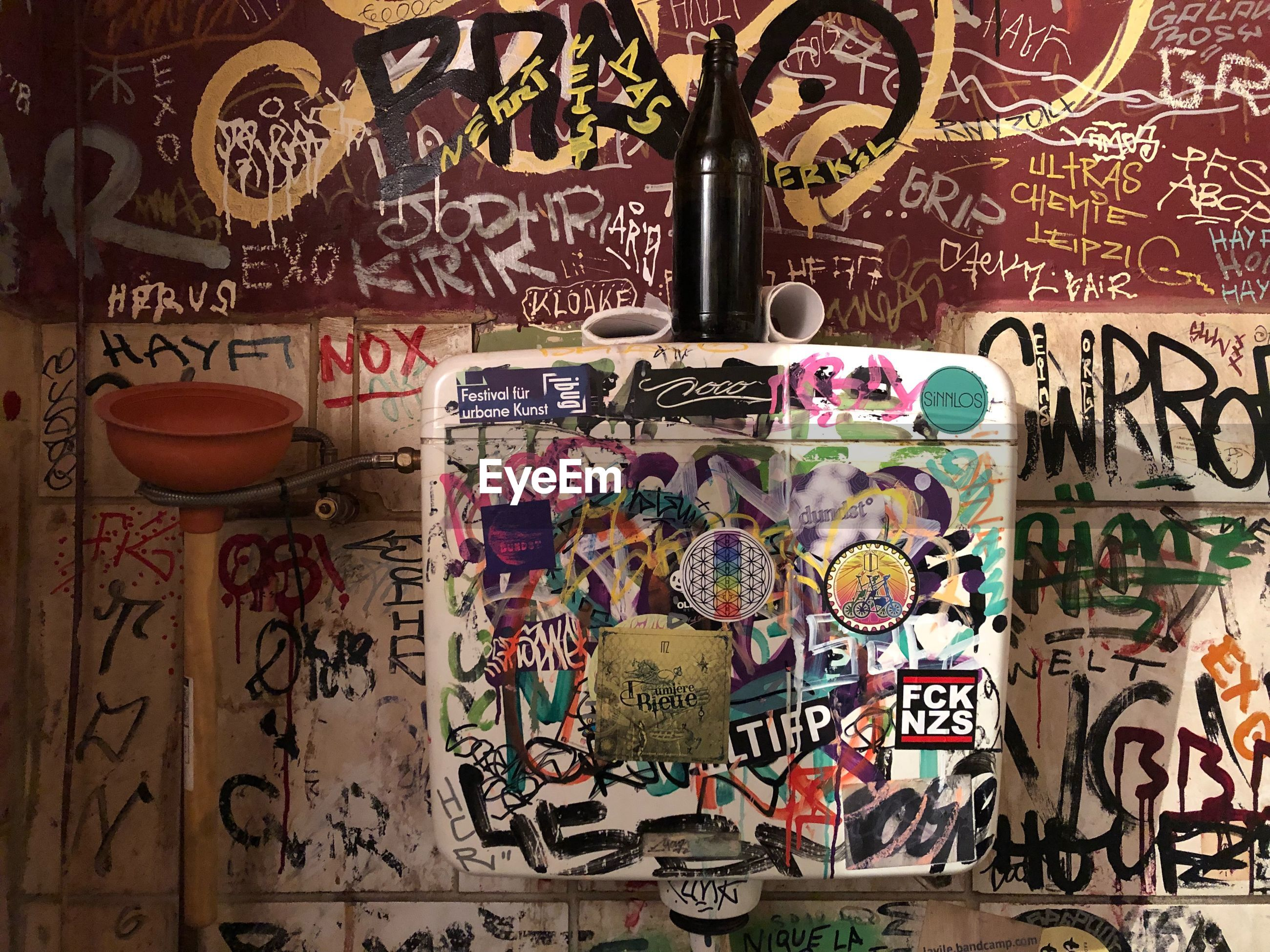 text, communication, no people, wall - building feature, graffiti, western script, art and craft, multi colored, variation, choice, creativity, indoors, representation, human representation, pattern, script, non-western script, wall, architecture, messy, floral pattern, message