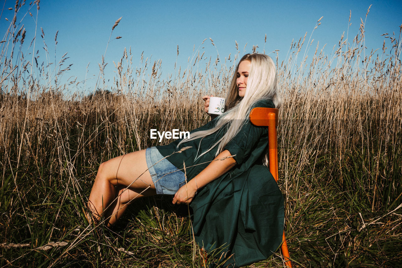 Young woman with mug sitting on chair amidst grass