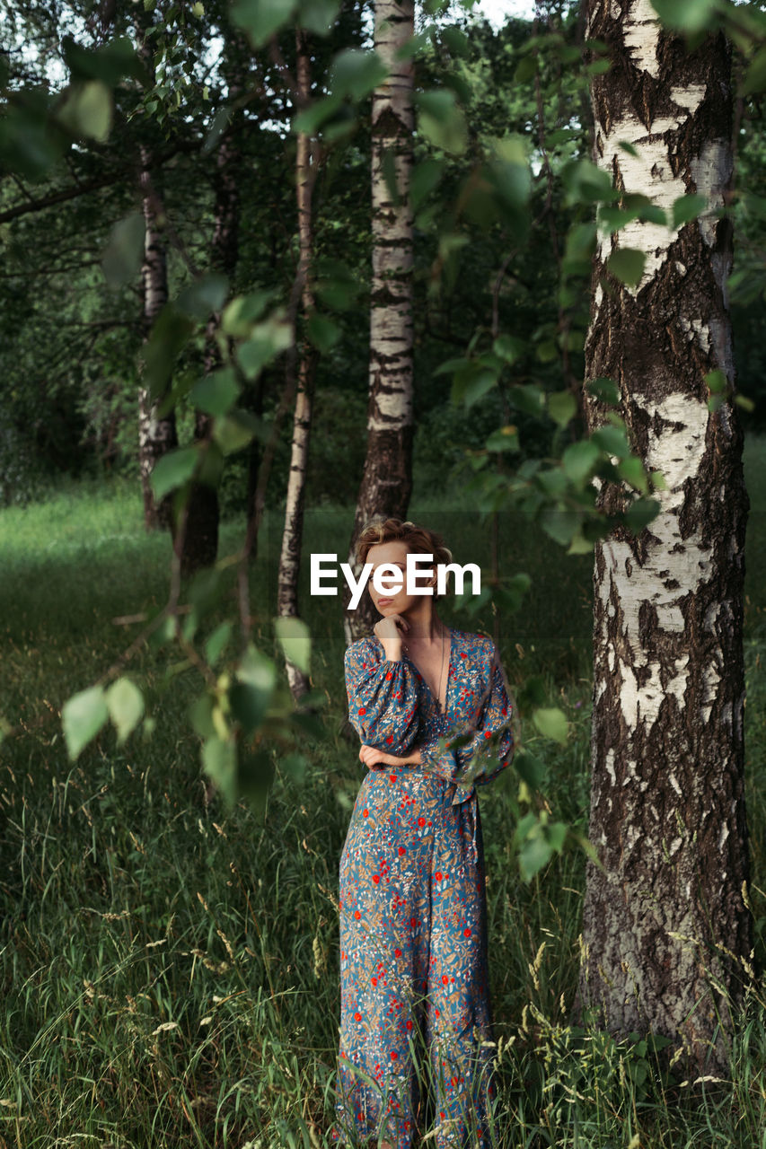 Woman standing against trees in forest