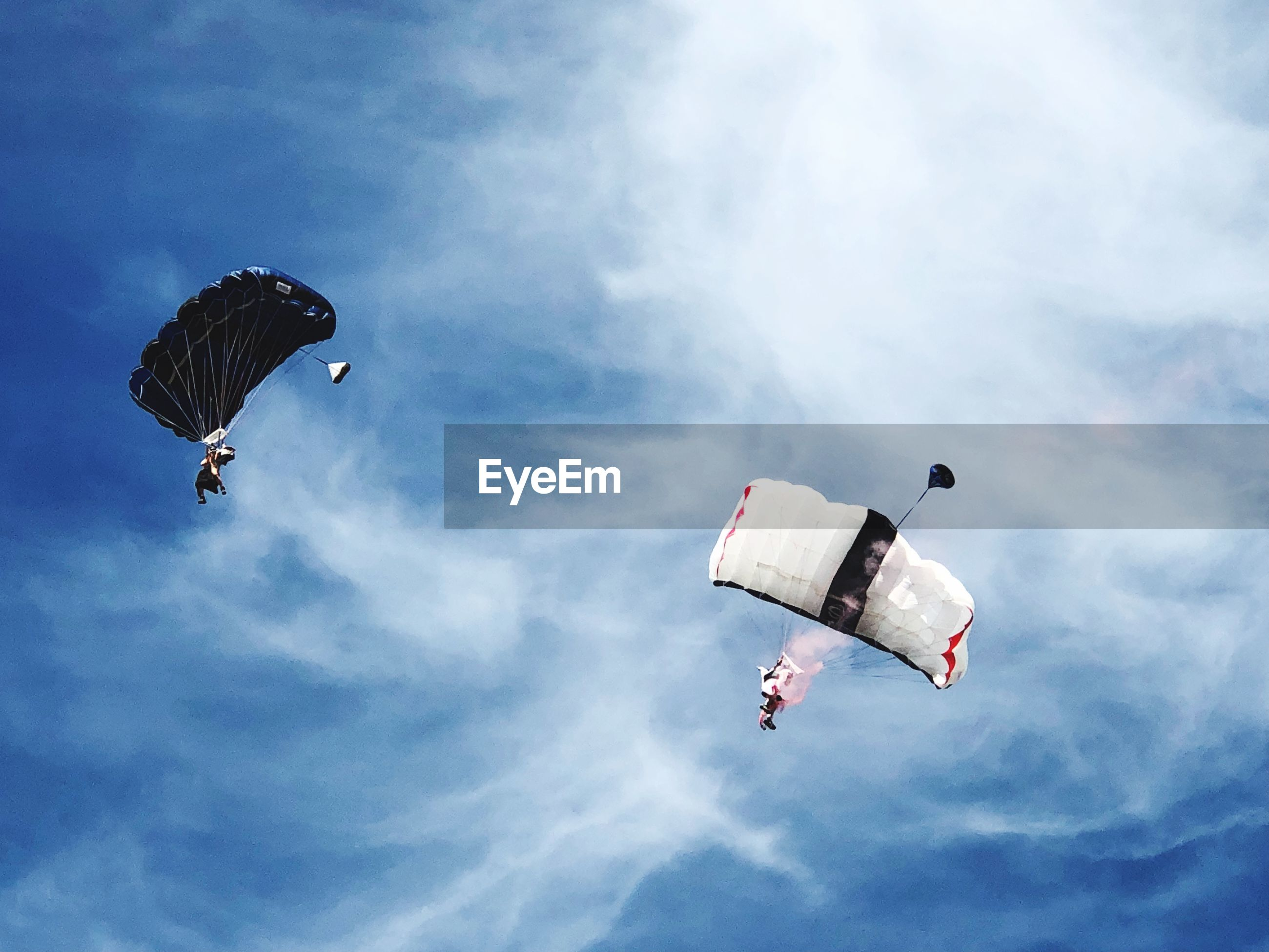 Low angle view of people paragliding