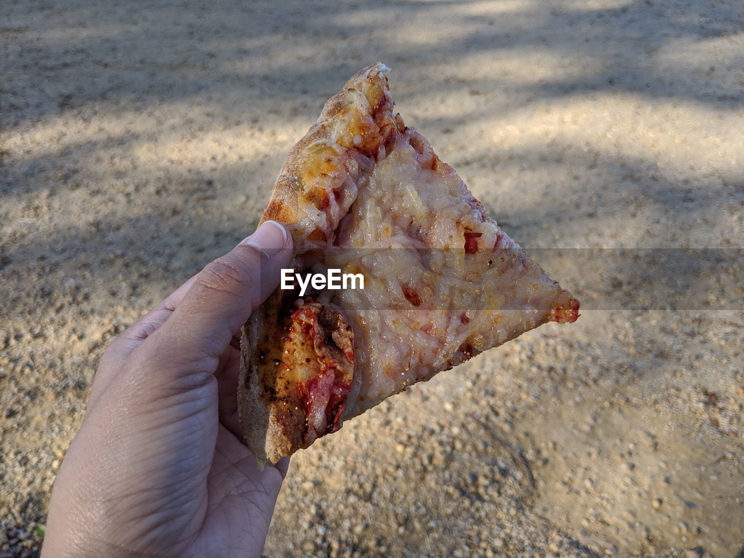 Pizza in hand, outdoors