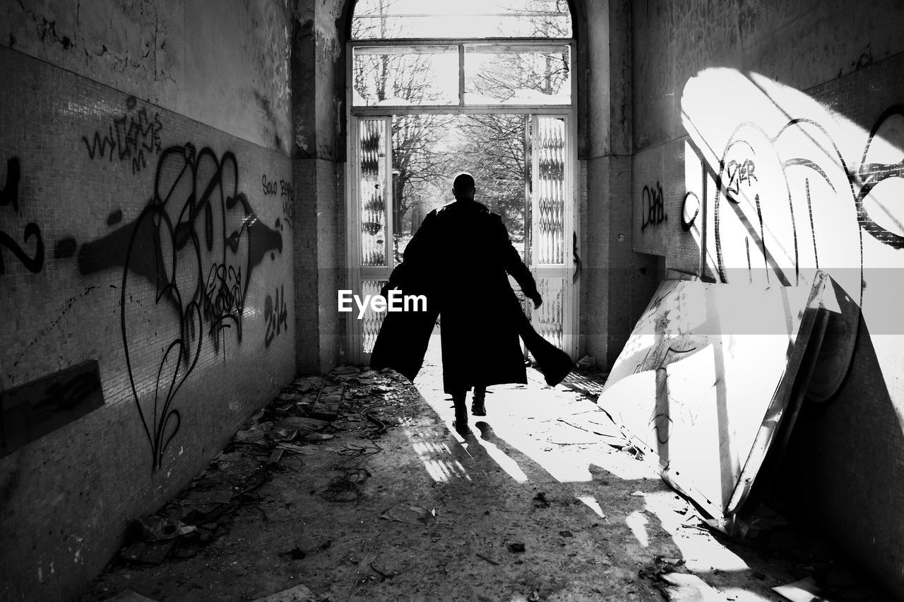 architecture, one person, real people, graffiti, rear view, wall - building feature, built structure, building, day, full length, lifestyles, men, walking, abandoned, indoors, window, nature