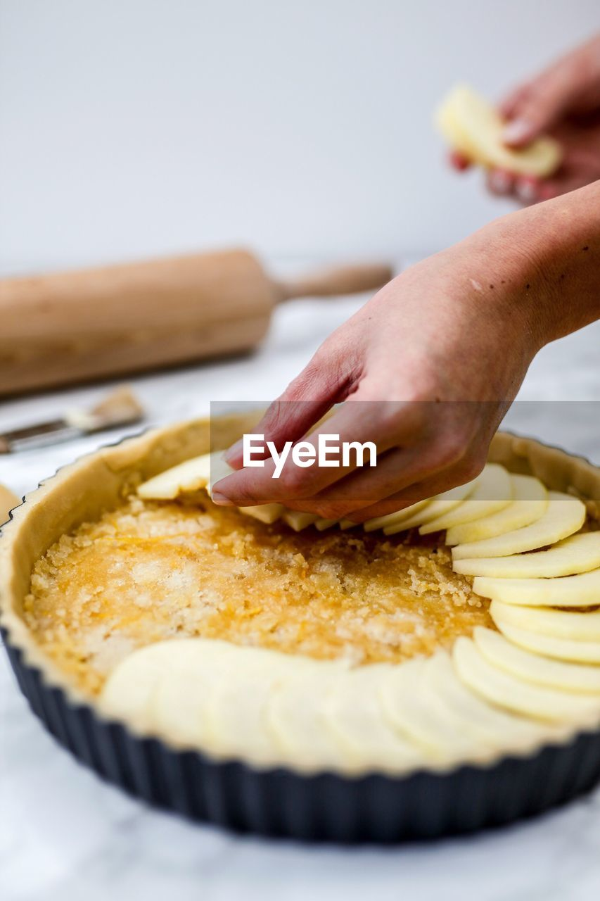 Close-Up Of Person Preparing Apple Pie