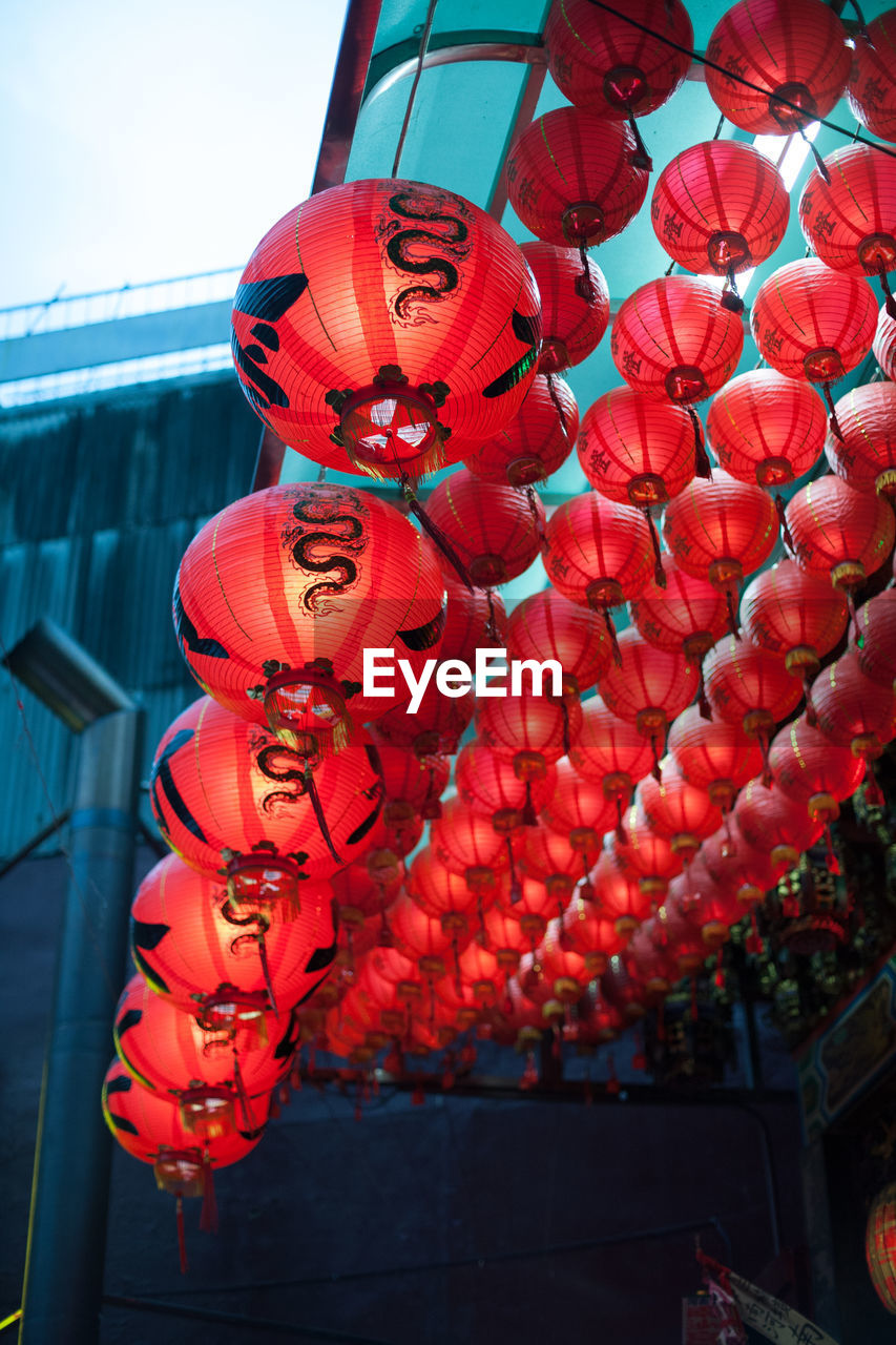 RED LANTERNS HANGING ON CLOTHESLINE AGAINST WALL