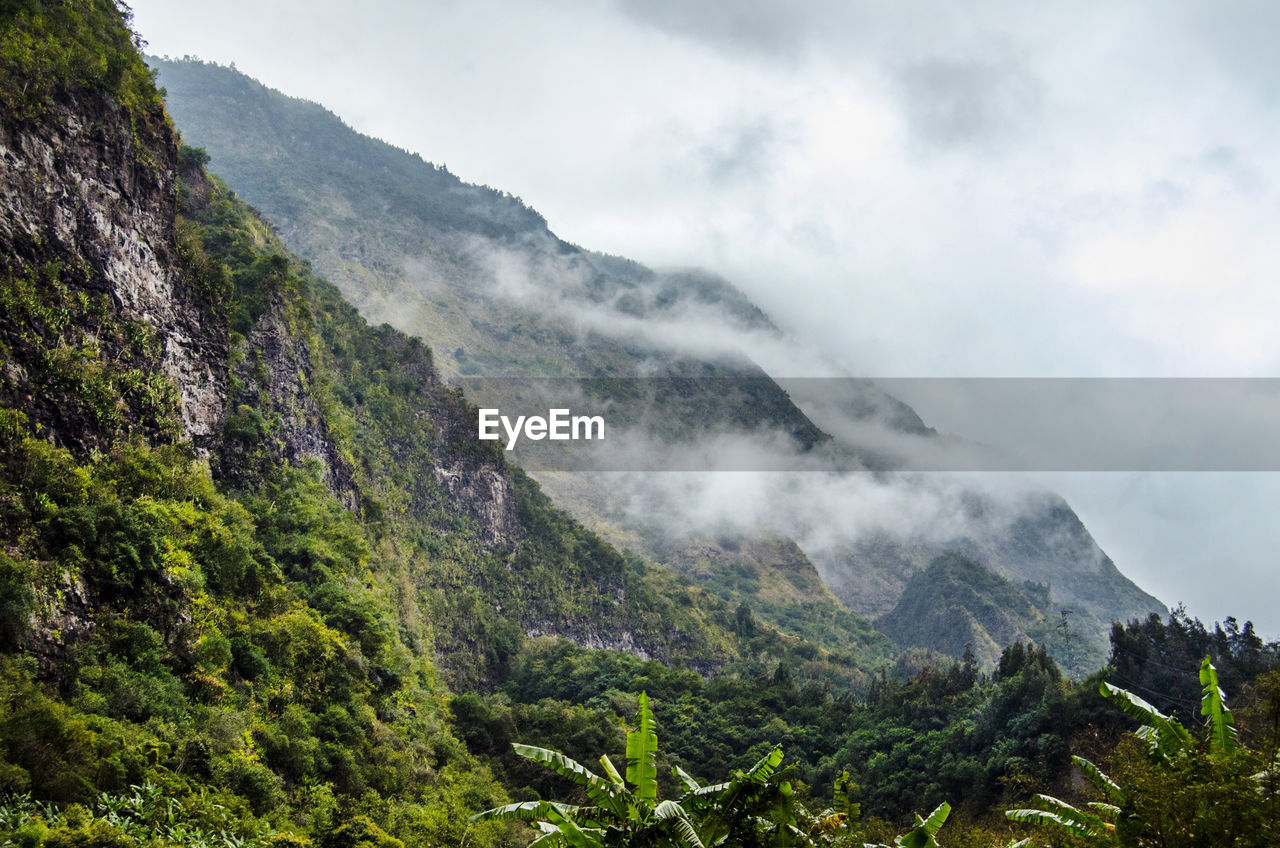 Scenic View Of Grassy Mountains Against Cloudy Sky