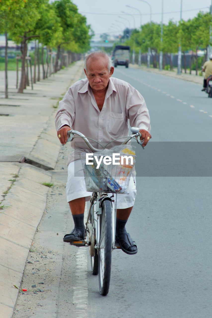 senior adult, bicycle, senior men, cycling, one person, transportation, full length, riding, casual clothing, front view, motion, real people, men, road, lifestyles, outdoors, leisure activity, day, happiness, one man only, only men, young adult, adult, people, adults only