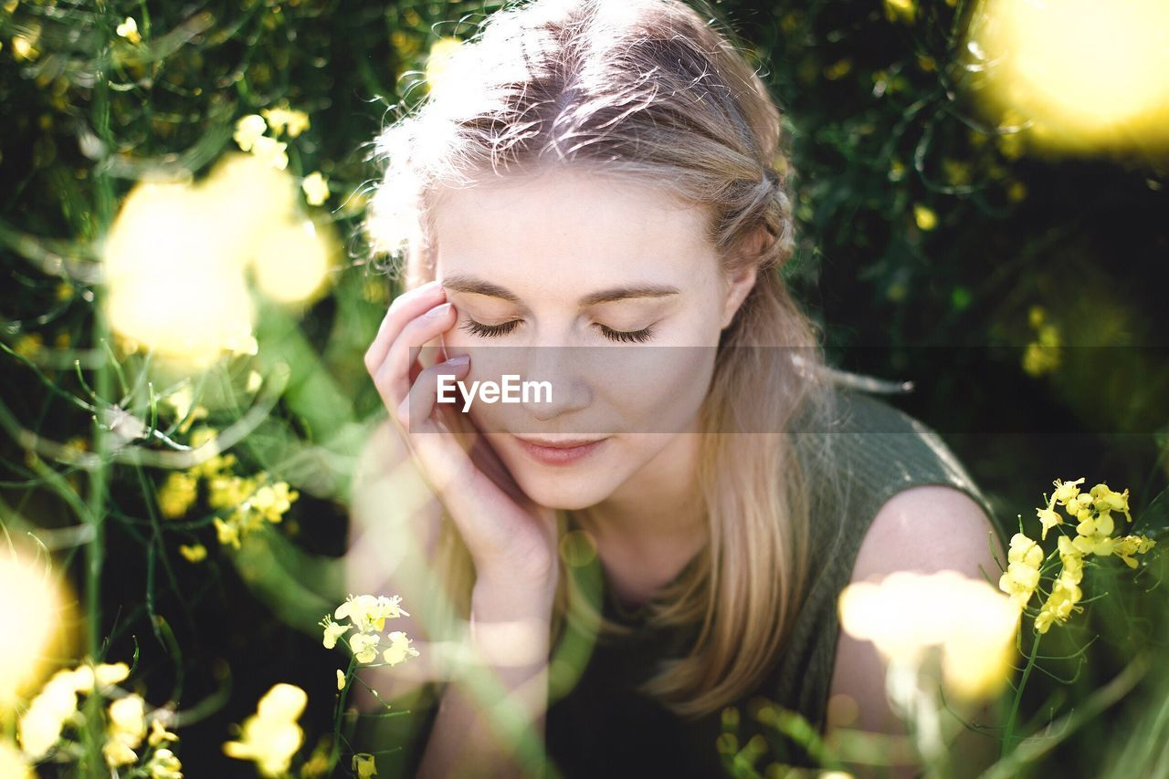 one person, blond hair, front view, young adult, eyes closed, outdoors, young women, day, looking down, nature, focus on foreground, real people, sunlight, flower, plant, leisure activity, headshot, beautiful woman, close-up, growth, fragility, tree