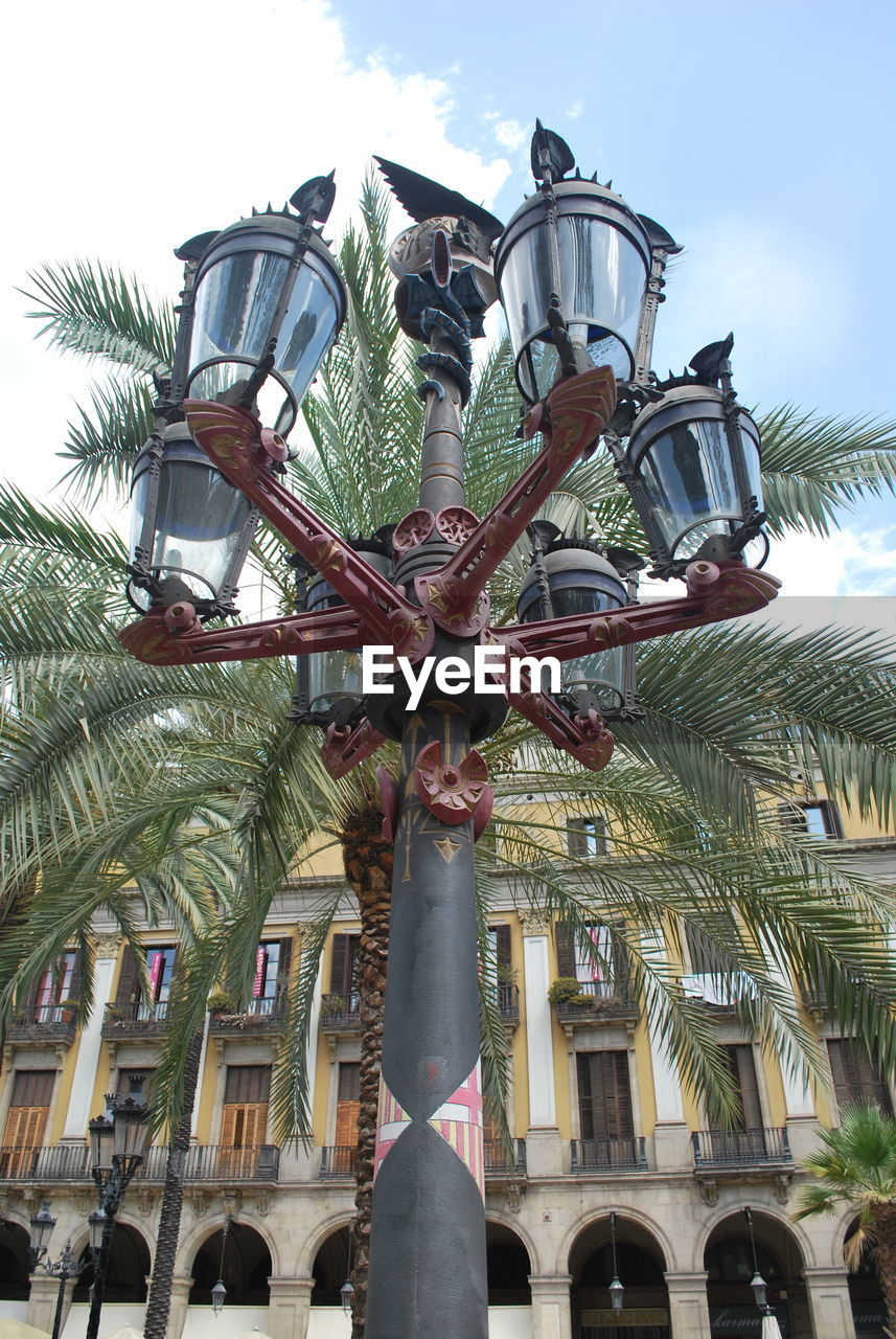 low angle view, architecture, built structure, building exterior, day, outdoors, sky, no people, palm tree, statue