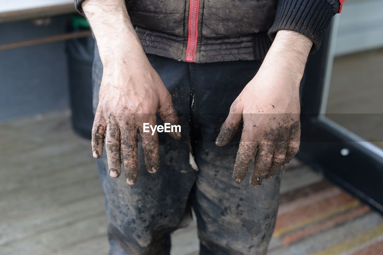 Midsection of worker wearing dirty clothes