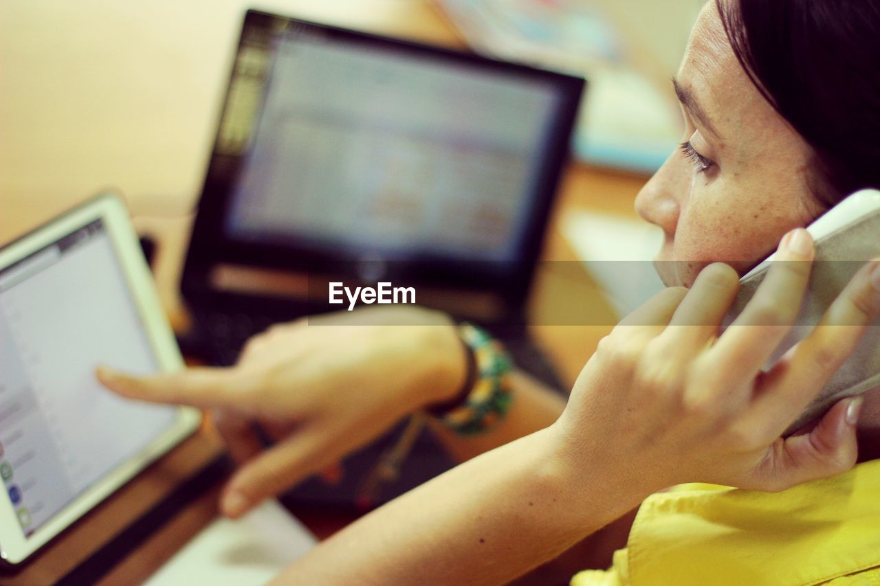 Cropped Image Of Woman Attending Call While Working In Office