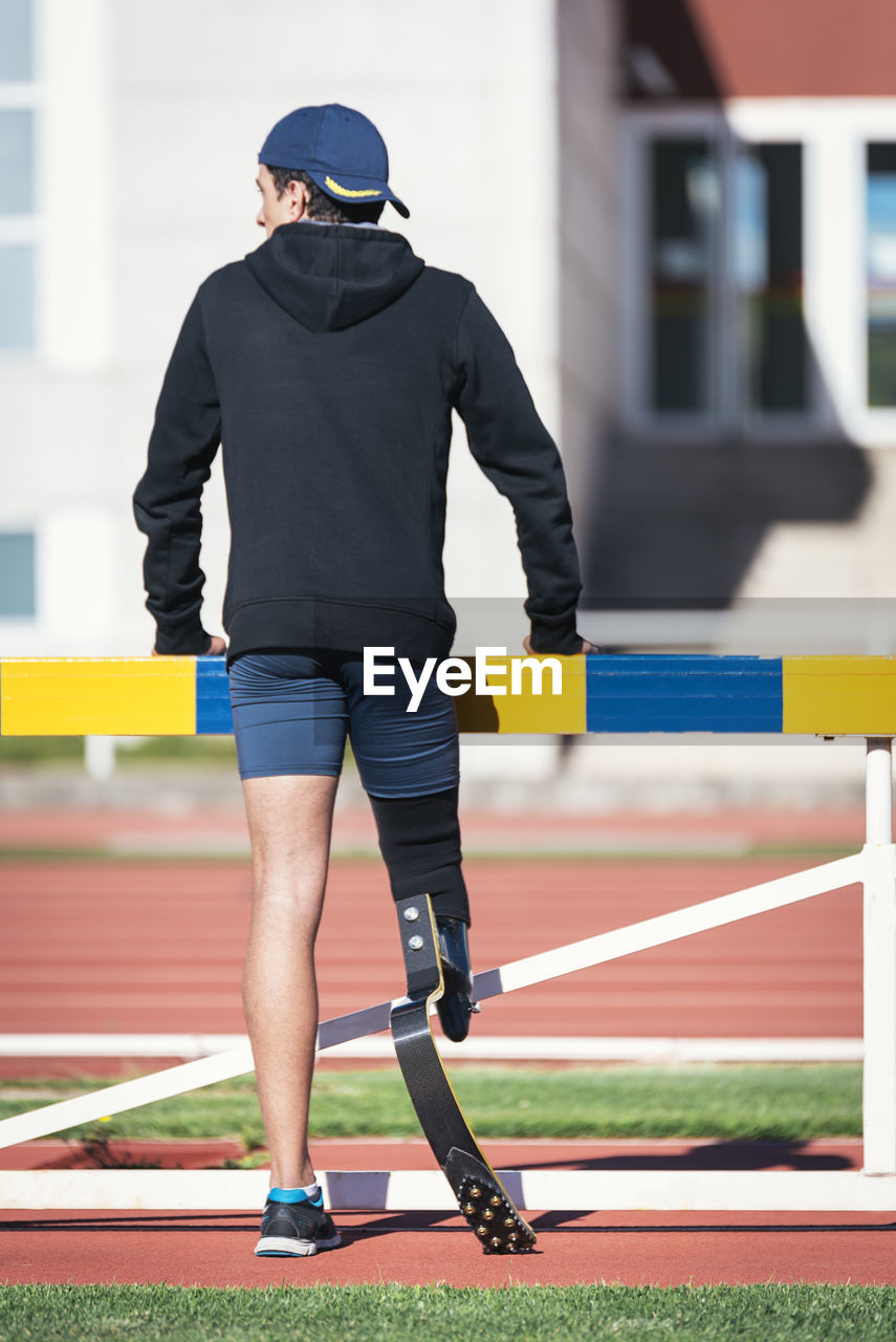 Rear view of athlete with prosthetic leg while standing by railing