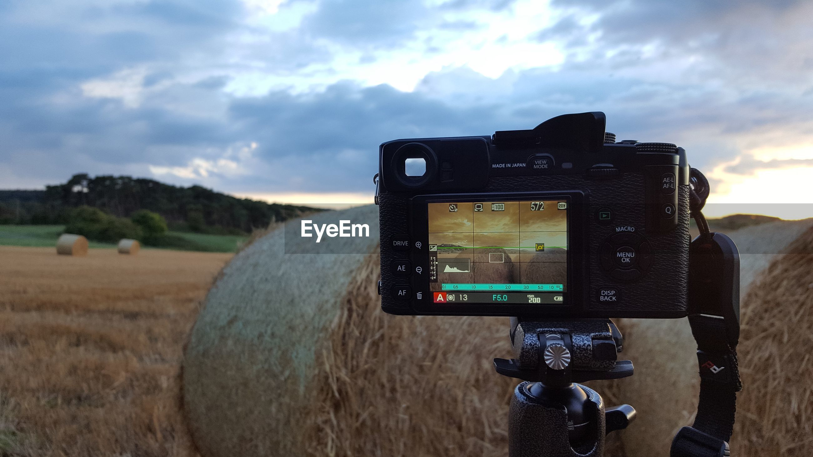 Close-up of camera by hay bale