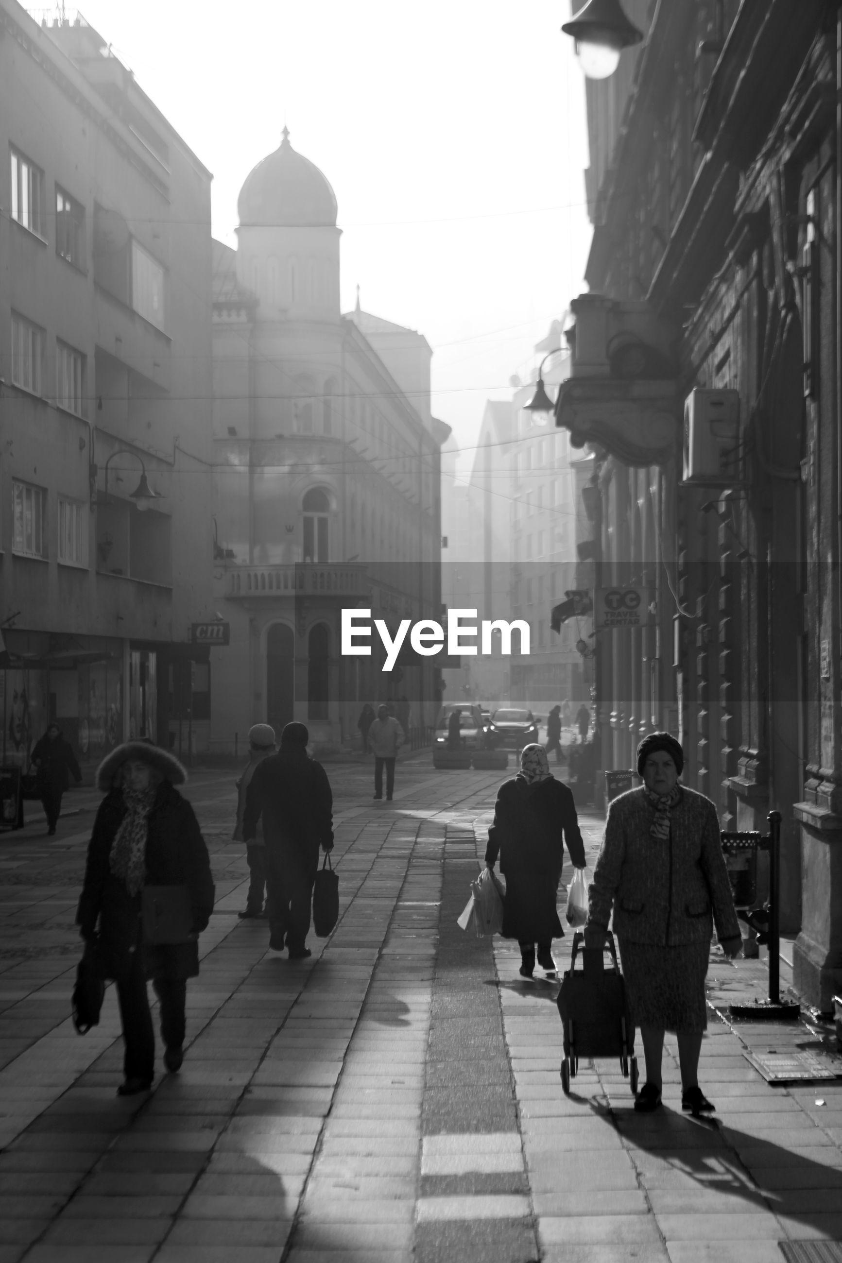 REAR VIEW OF PEOPLE WALKING ON STREET IN CITY