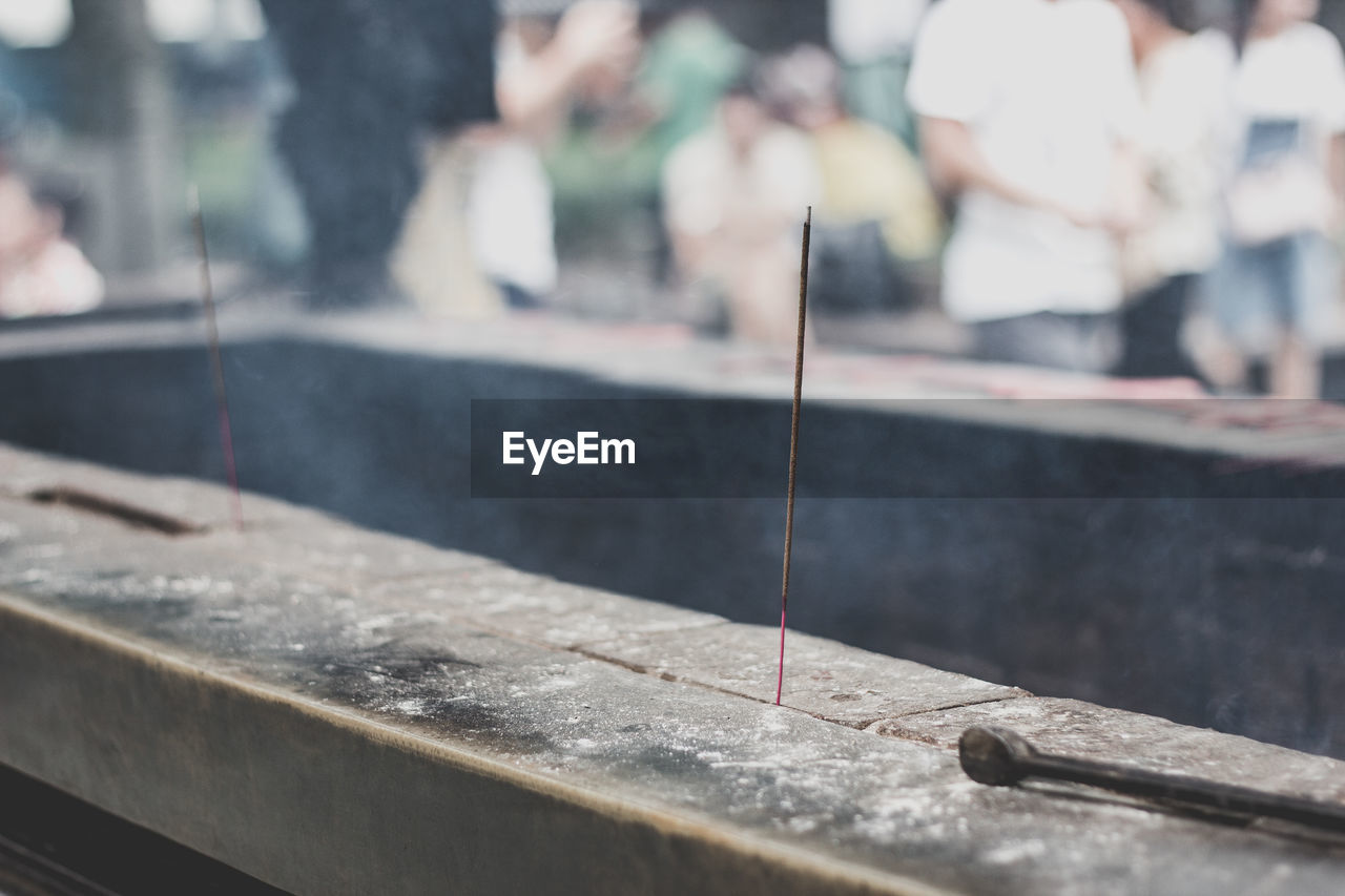 Close-Up Of Burning Incense Stick In Temple