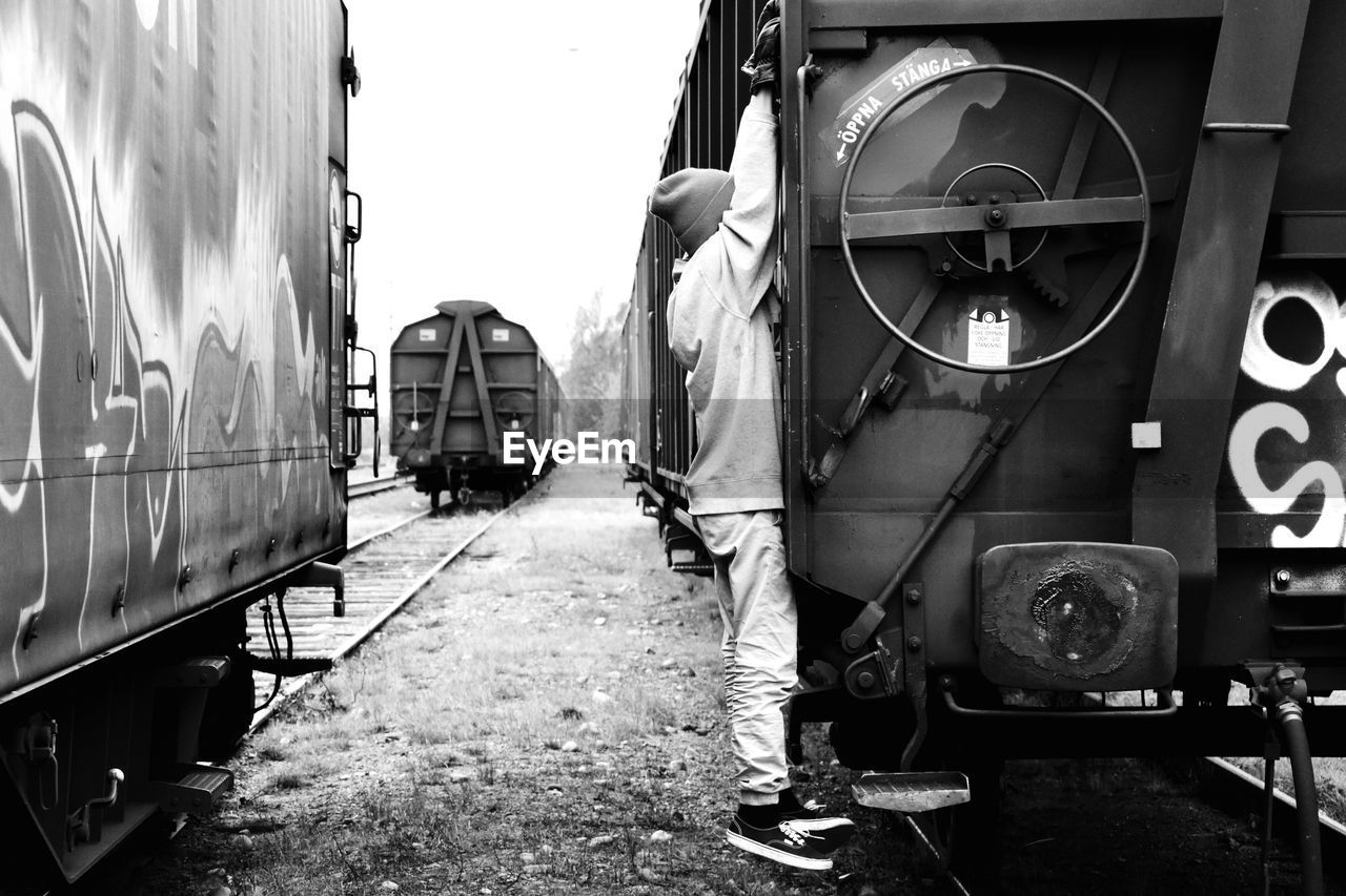 train, rail transportation, mode of transportation, train - vehicle, transportation, public transportation, railroad track, one person, track, day, real people, travel, land vehicle, full length, men, outdoors, architecture, standing, rear view, shunting yard, railroad car, wheel