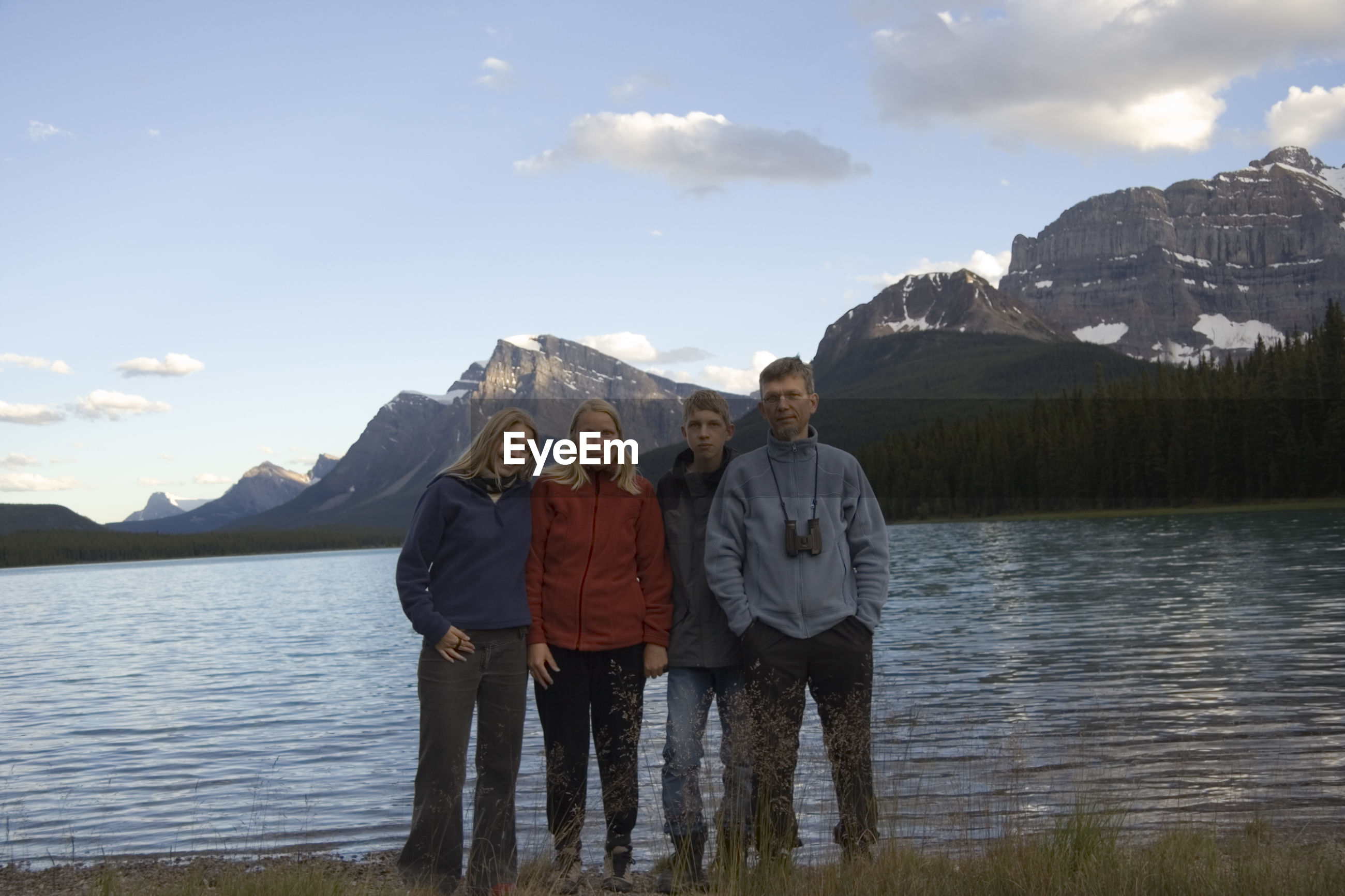 Portrait of family standing by lake waterfowl against sky at banff national park