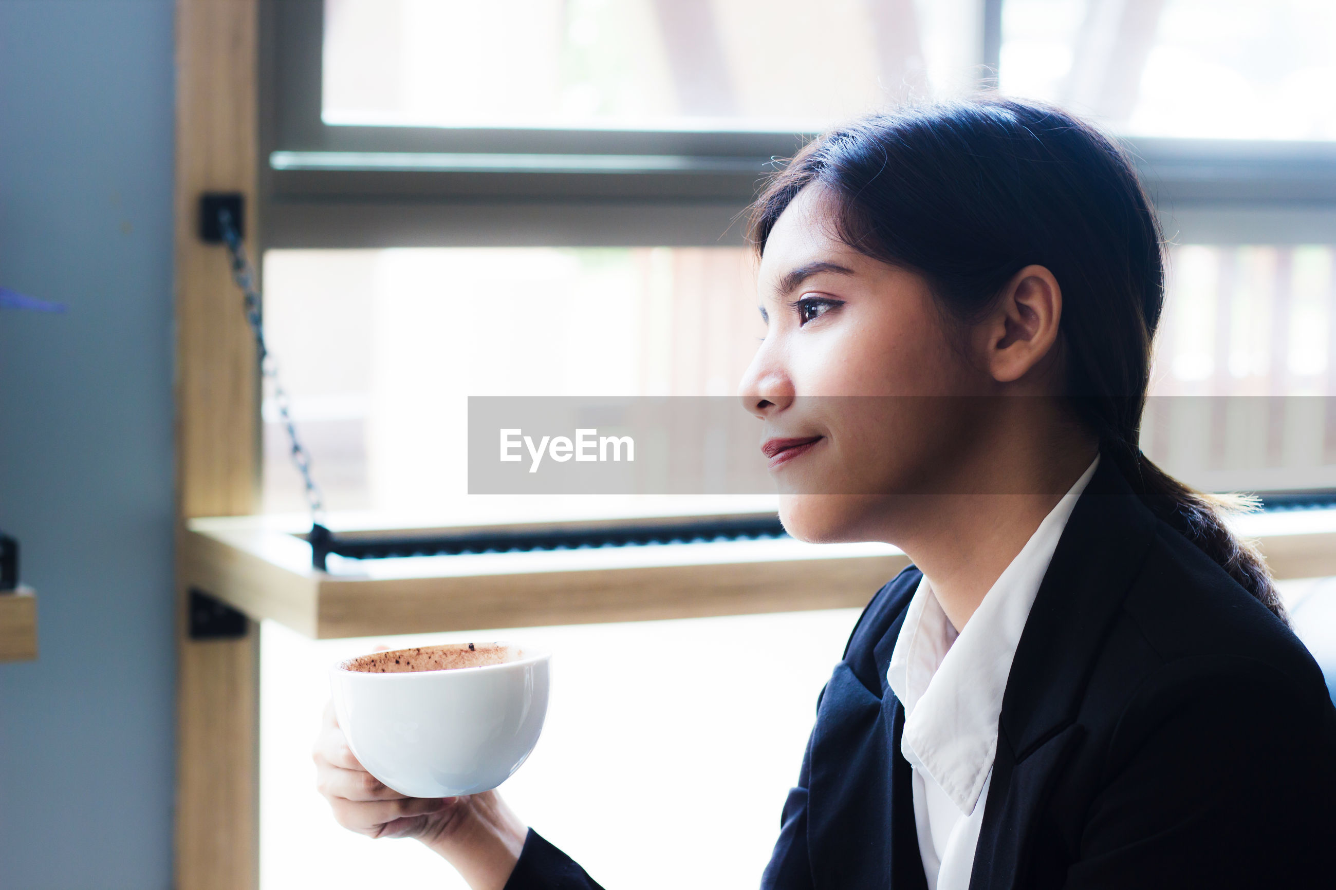 Confident businesswoman sitting with coffee mug at cafe