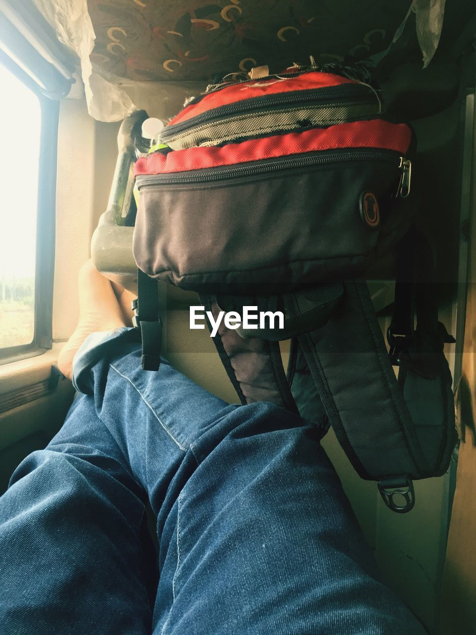 Midsection of man with luggage sitting in train