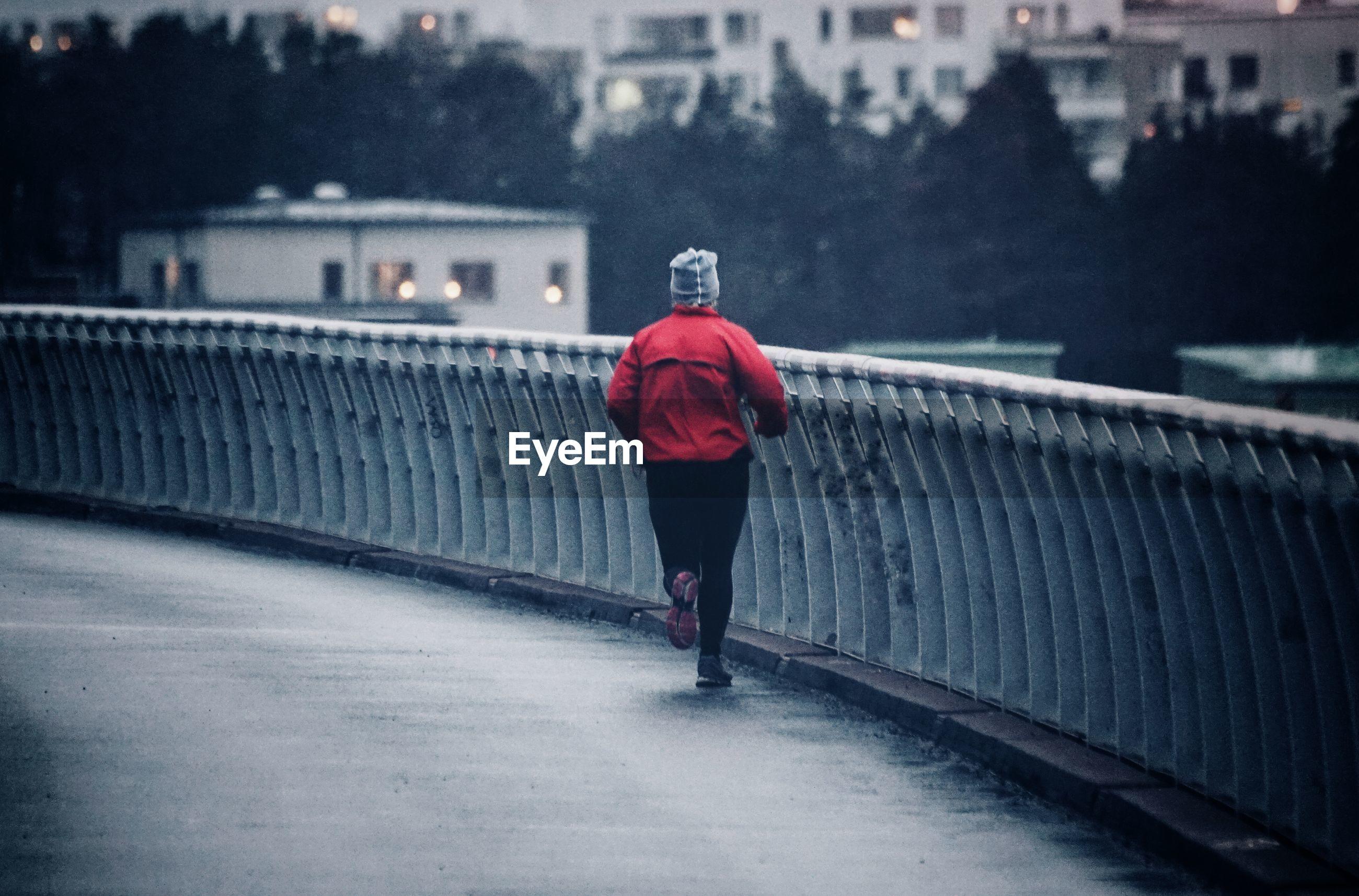 Rear view of woman running on bridge