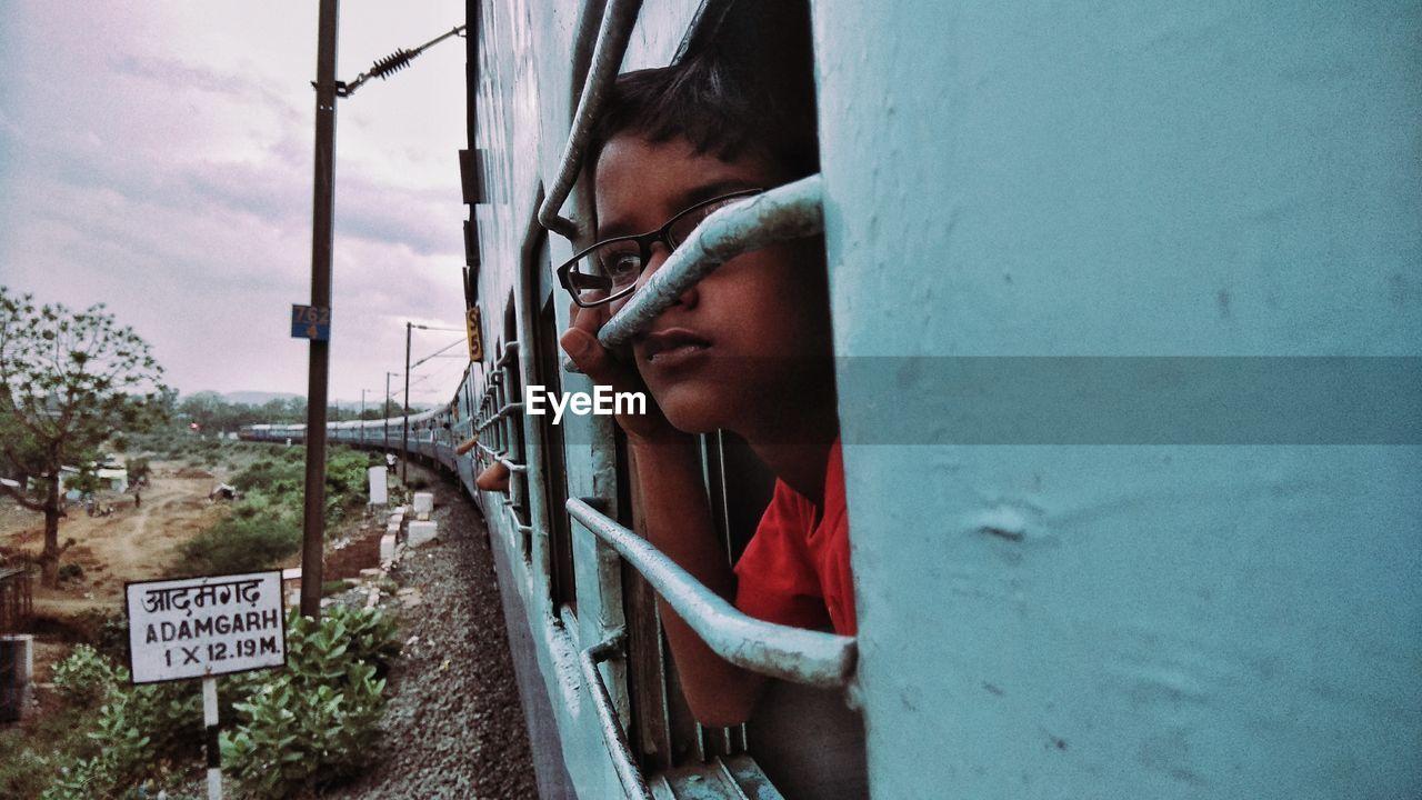 Close-Up Of Boy Looking Through Train Window
