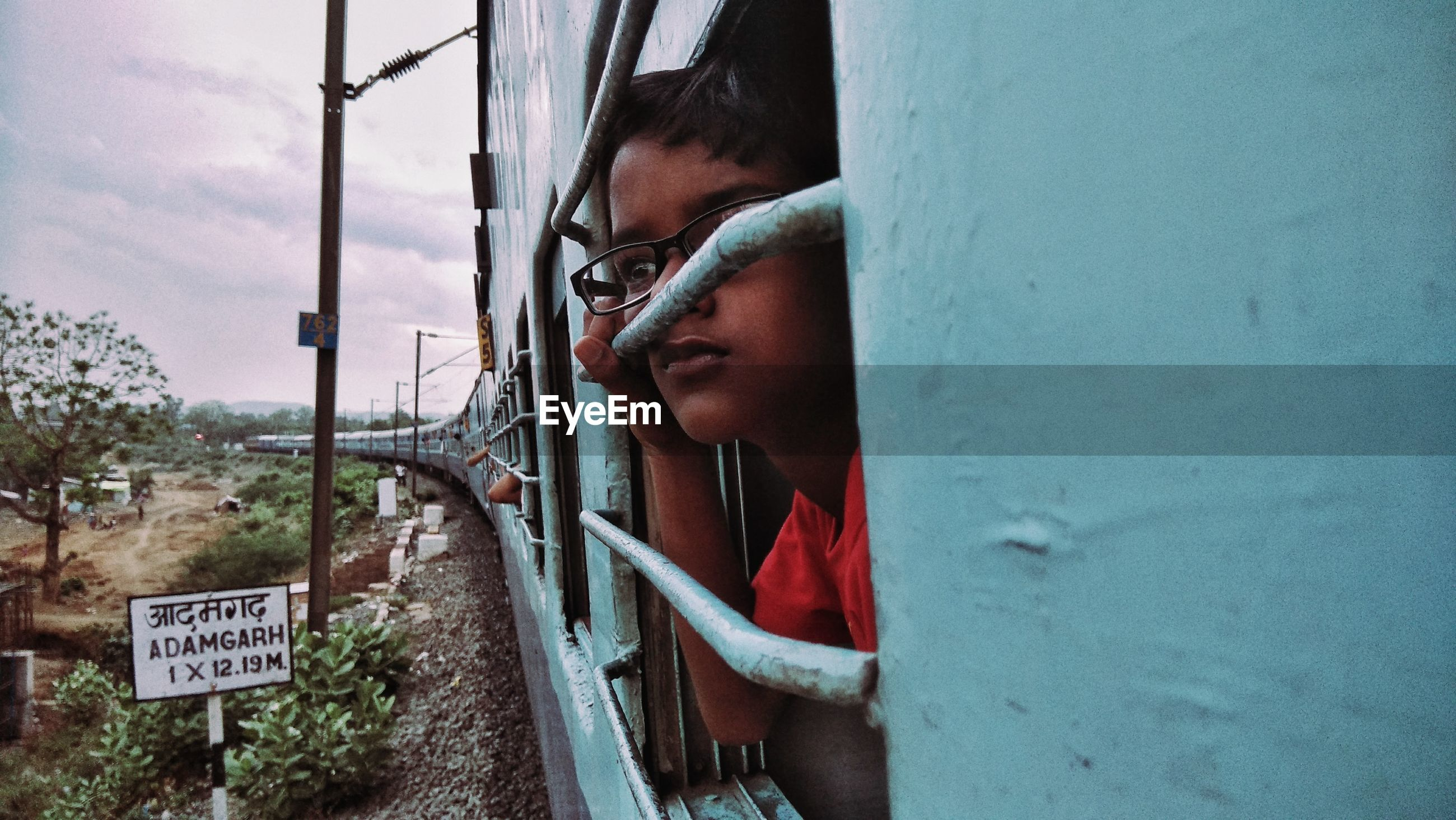 Close-up of boy looking through train window