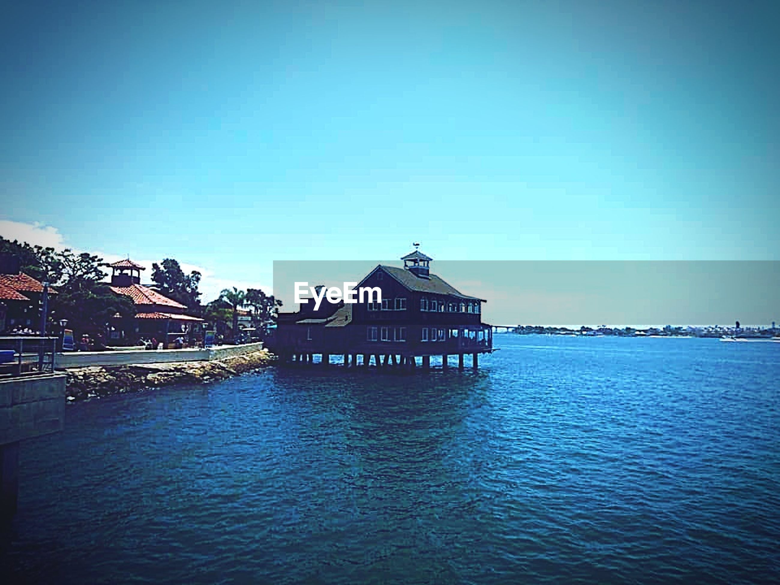 water, architecture, built structure, building exterior, sky, waterfront, clear sky, building, nature, no people, day, blue, sea, vignette, house, tranquility, copy space, rippled, tranquil scene, outdoors
