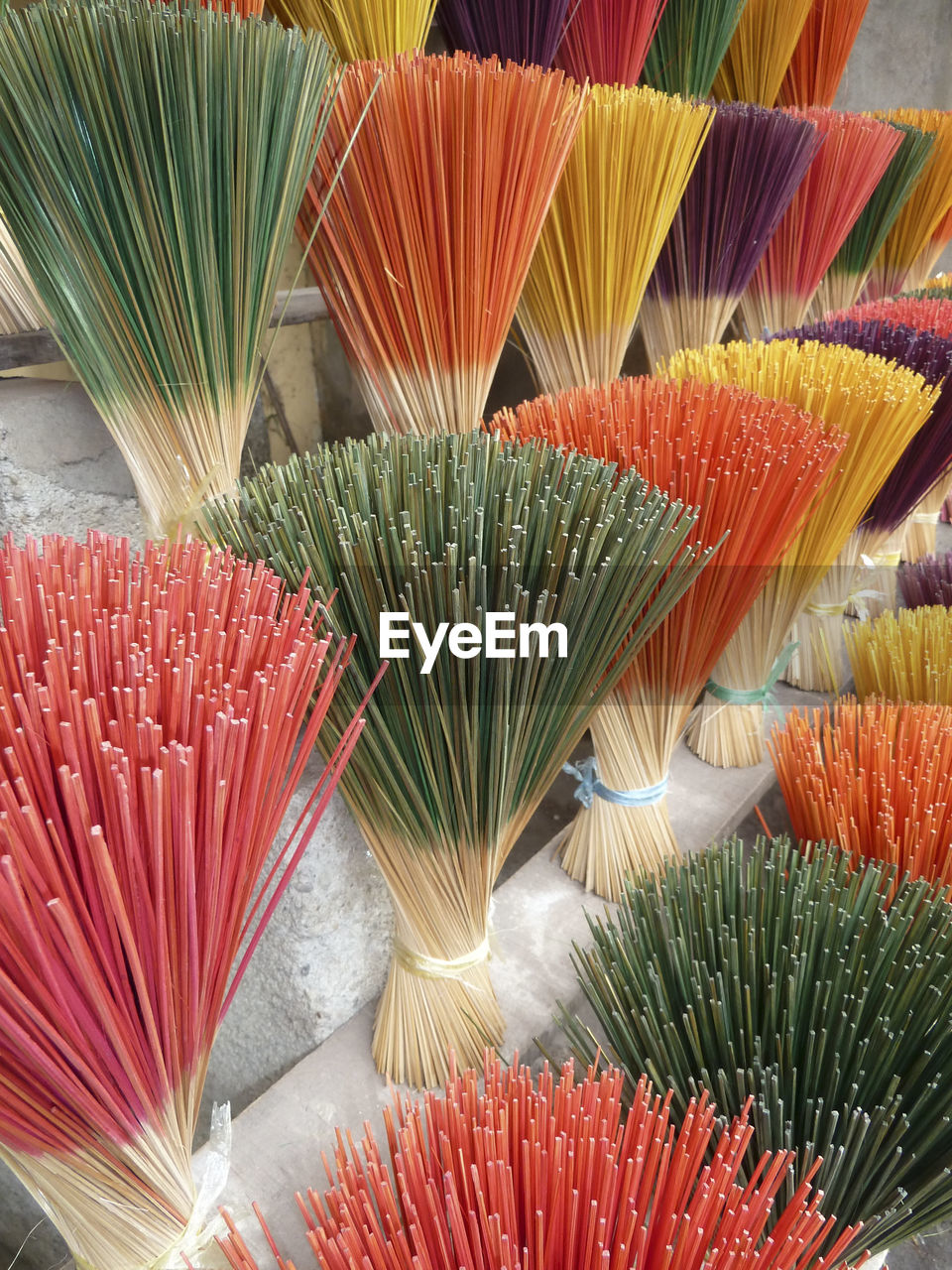 Close-up of multi colored brooms for sale in market