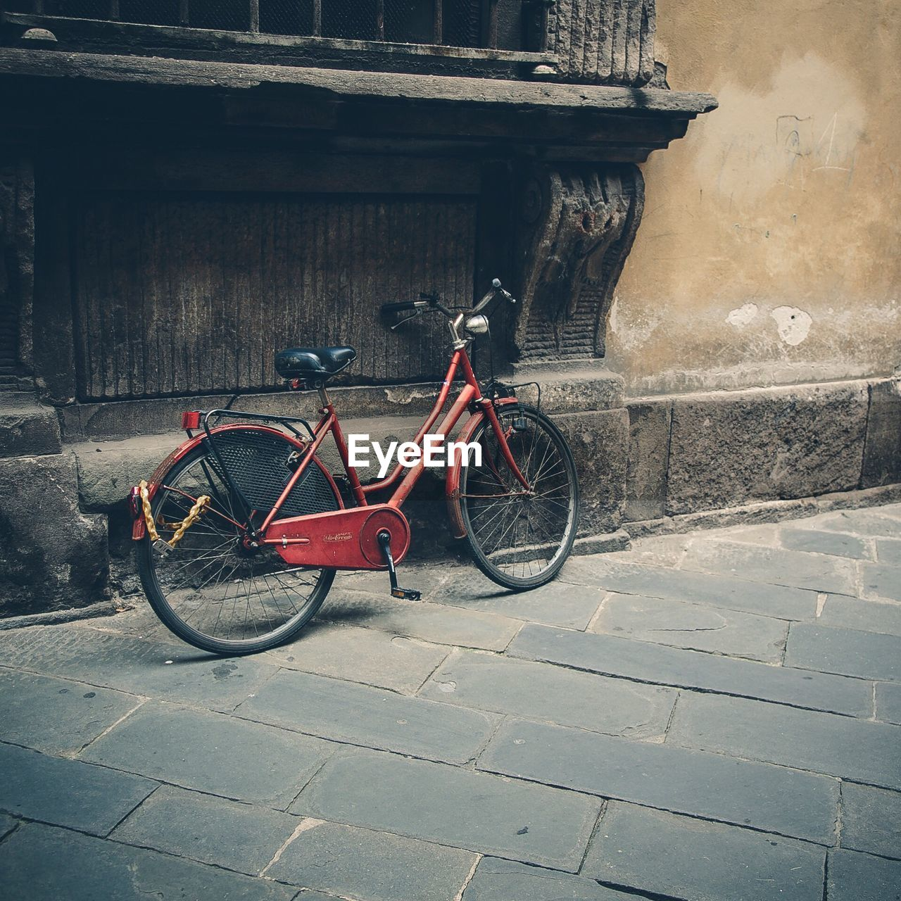 Red Bicycle Parked By Wall On Sidewalk