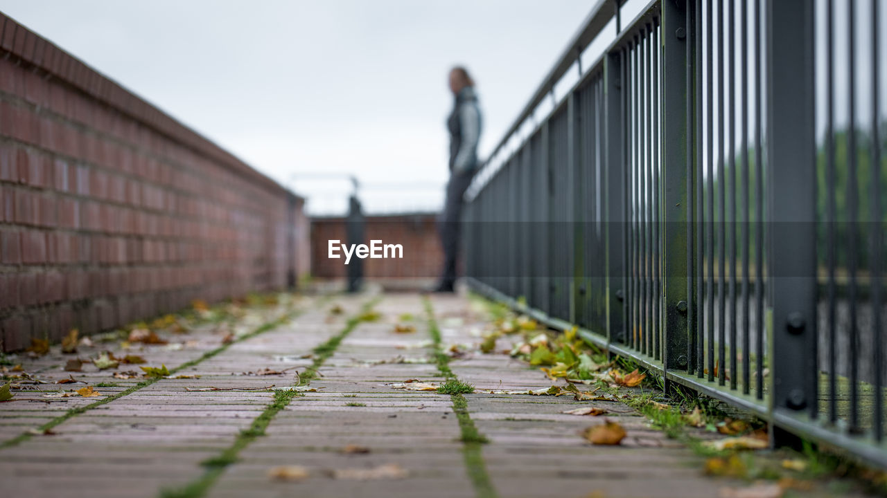 selective focus, the way forward, architecture, day, built structure, direction, footpath, focus on foreground, railing, nature, metal, barrier, outdoors, safety, sky, security, fence, boundary, transportation, diminishing perspective, surface level
