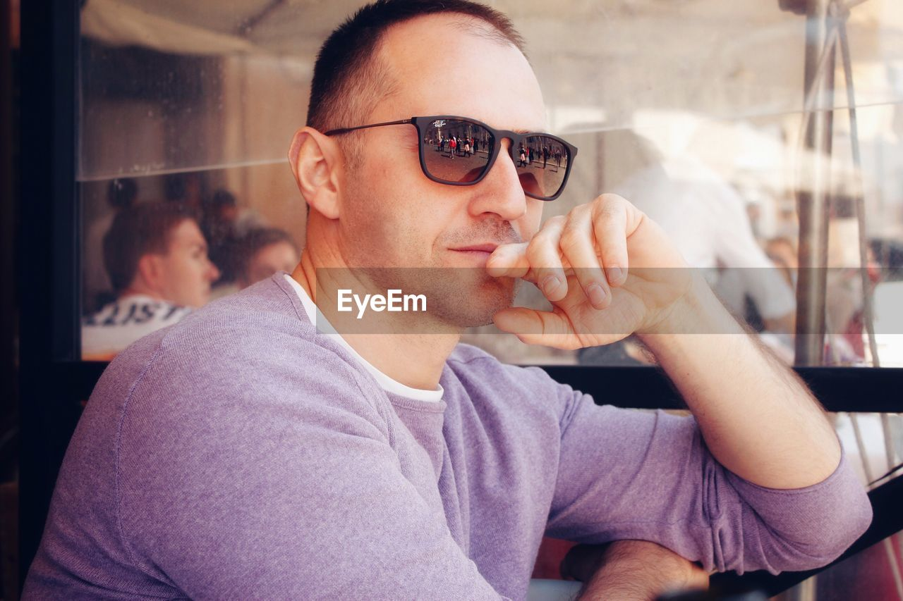 glasses, one person, real people, headshot, portrait, casual clothing, eyeglasses, front view, young adult, lifestyles, leisure activity, indoors, young men, focus on foreground, communication, sitting, sunglasses, holding, contemplation