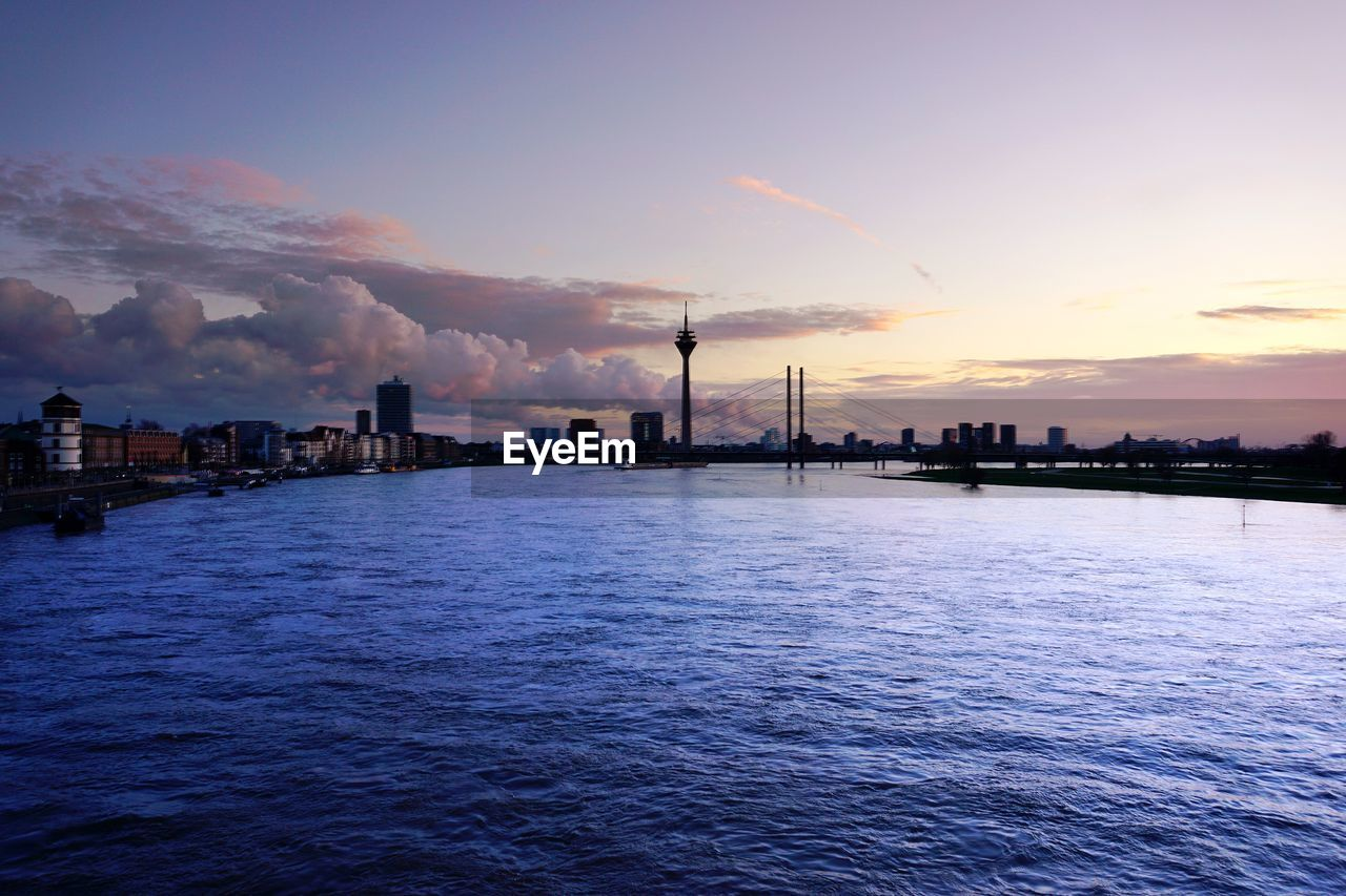 SCENIC VIEW OF SEA BY CITY AGAINST SKY DURING SUNSET