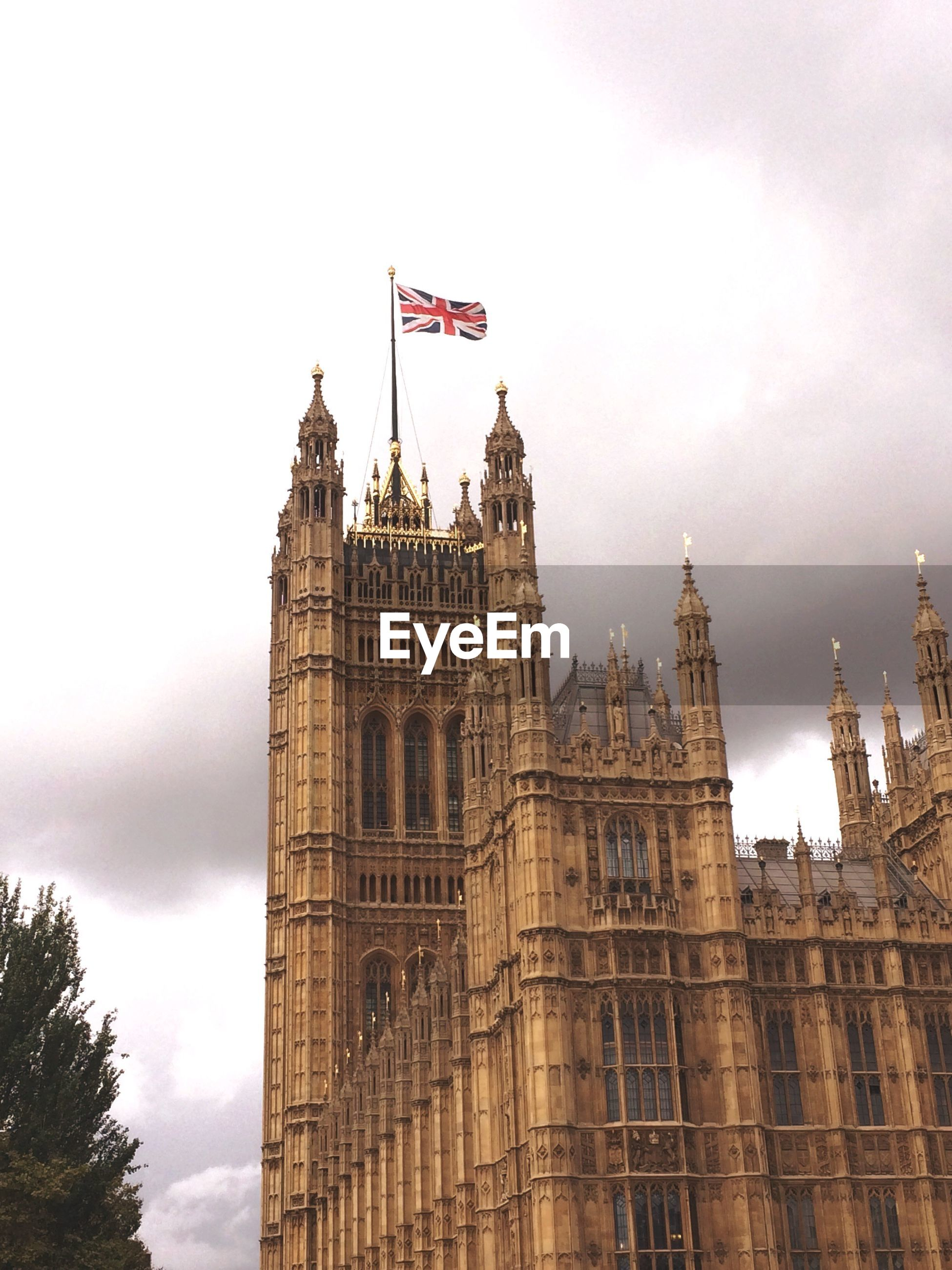 architecture, built structure, building exterior, big ben, sky, travel destinations, parliament building, history, government, government building, low angle view, cloud - sky, flag, clock tower, famous place, tourism, tower, gothic style, city, culture, international landmark, houses of parliament, cloud, atmospheric mood, city life, outdoors, tall - high, high section, capital cities, cloudy, spire