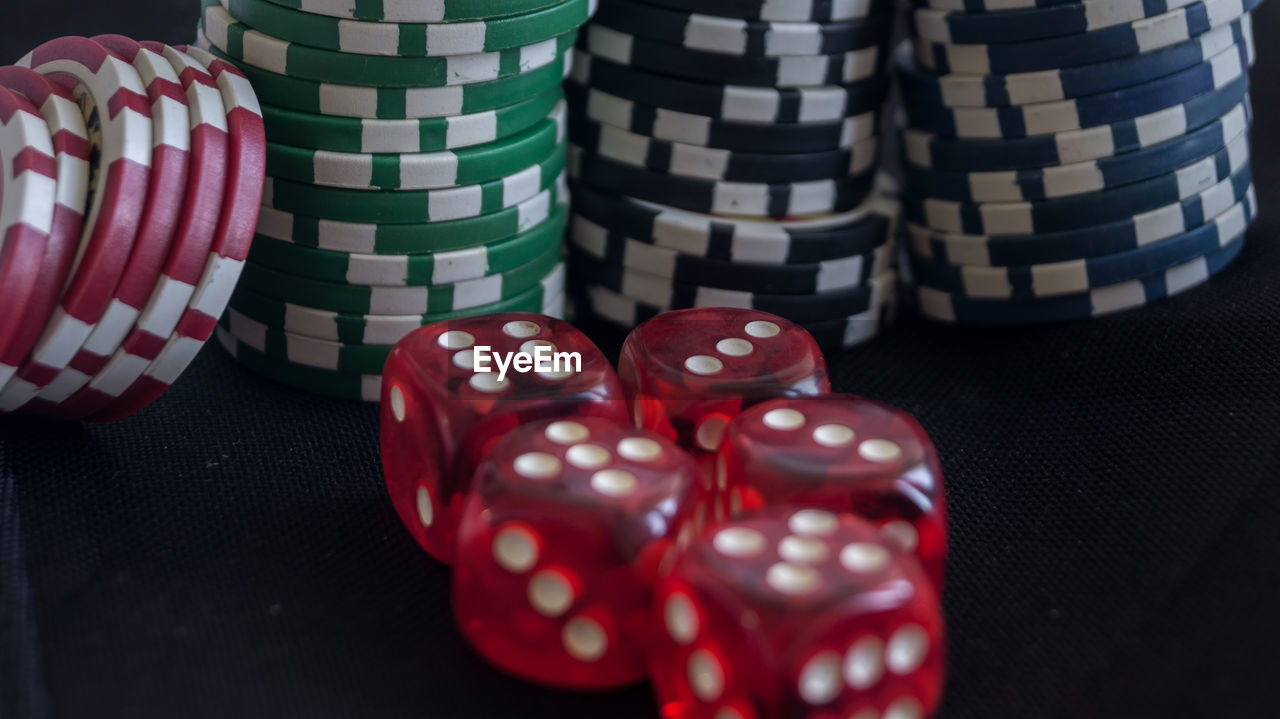 Close-Up Of Red Dice And Gambling Chips On Black Table